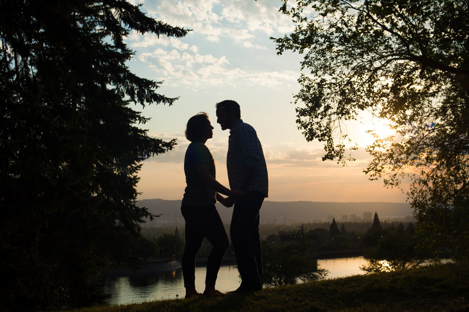 a couple stand silhouetted in front of a pretty sunset at mt tabor