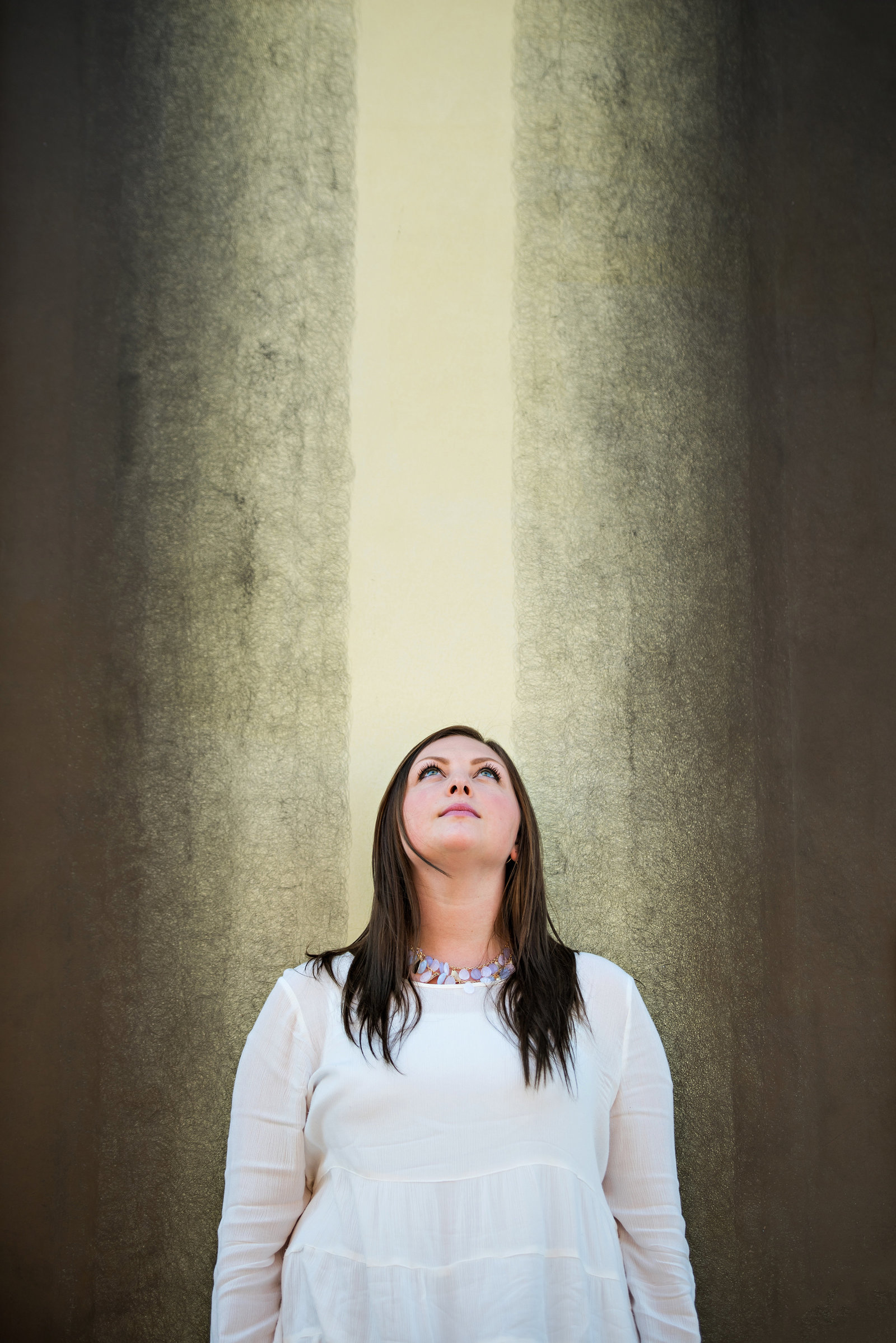A woman in front of wall art looks up to the sky.