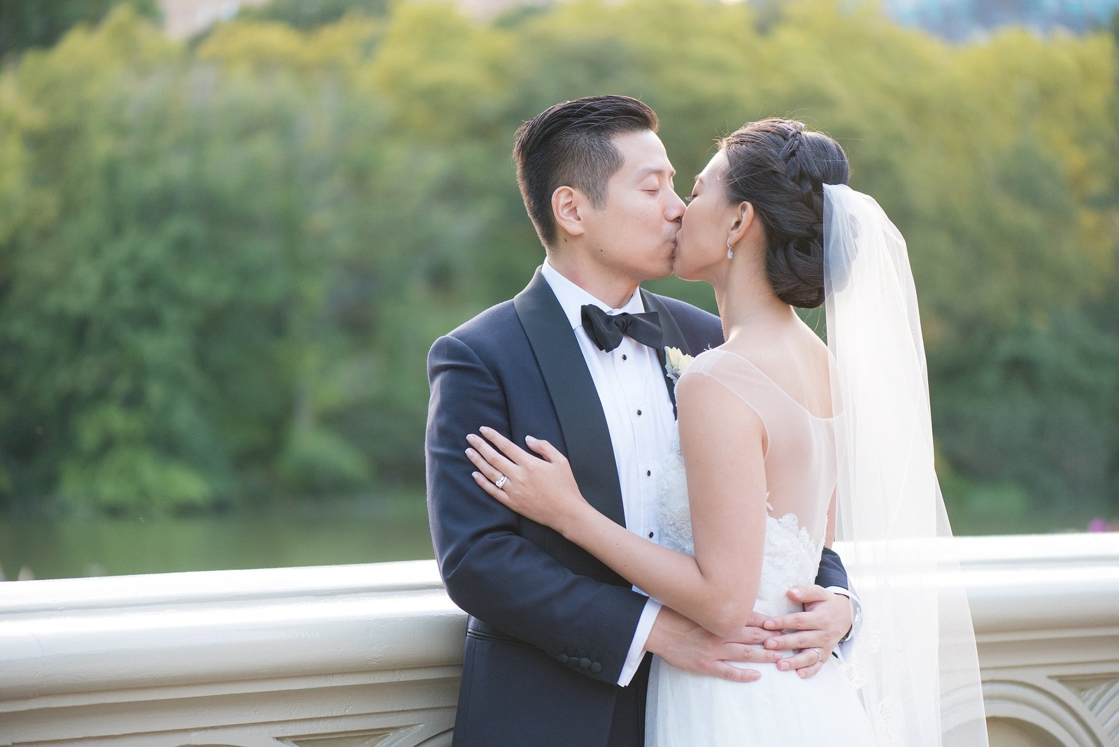 Asian Bride and Groom Kissing on Bow Bridge in Central Park, New York City Photo