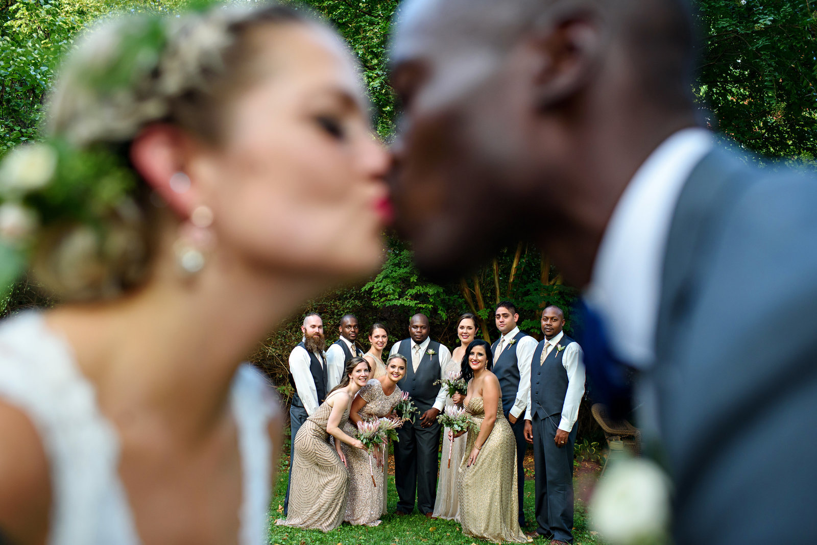 The wedding party in between the out of focus bride and groom kissing.