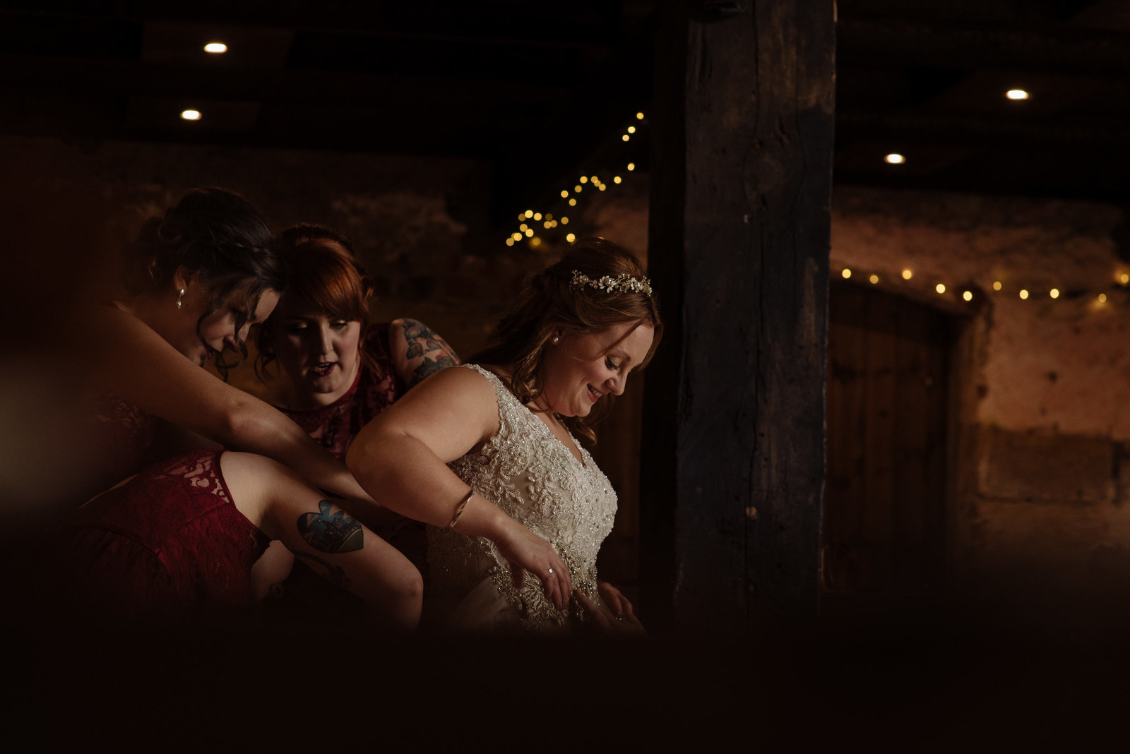 Bride putting on wedding gown with bridesmaids in the barn at Camp Katur. Documentary fine art wedding photographer