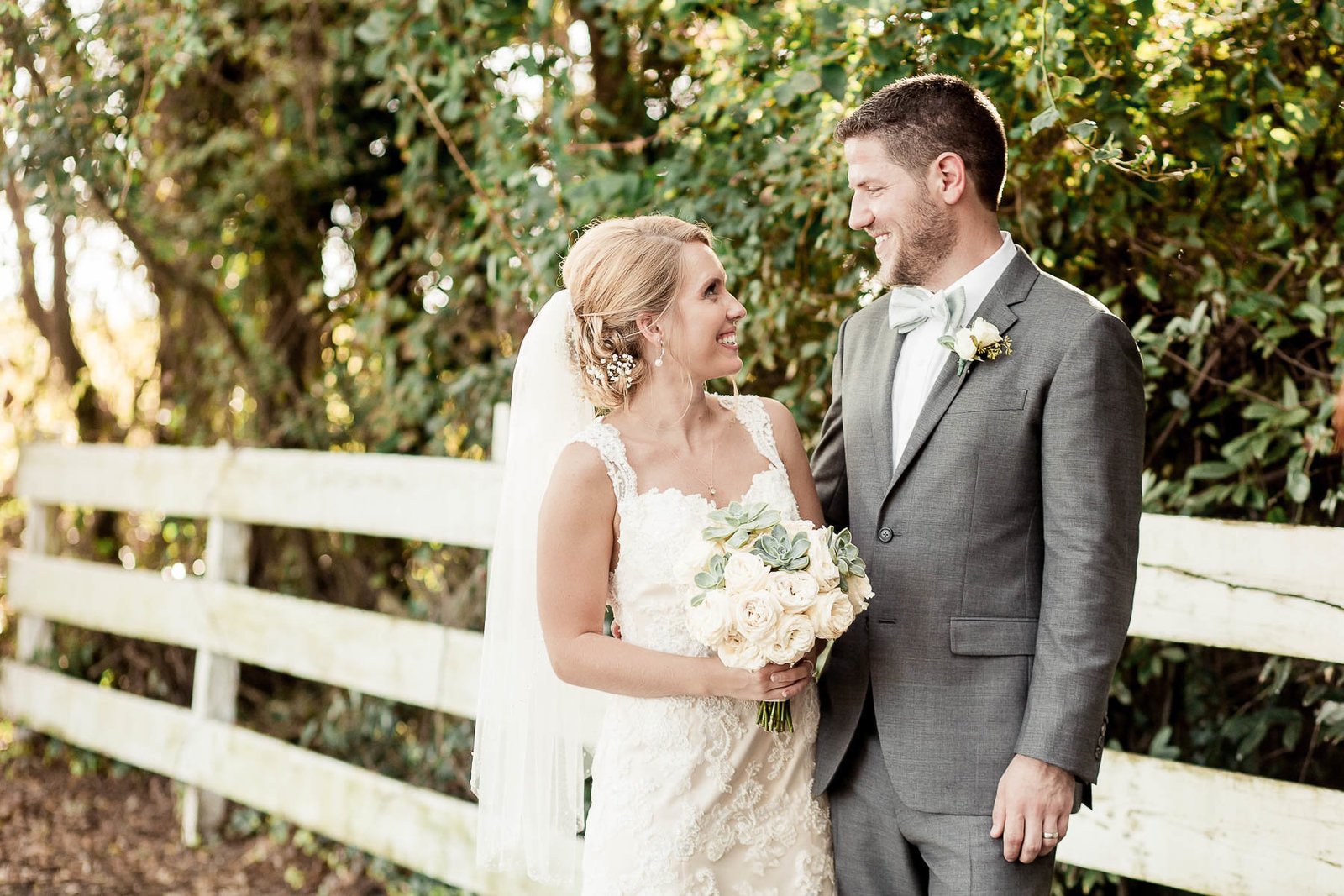 Bride and groom stand by white picket fence, Alhambra Hall, Mt Pleasant, South Carolina