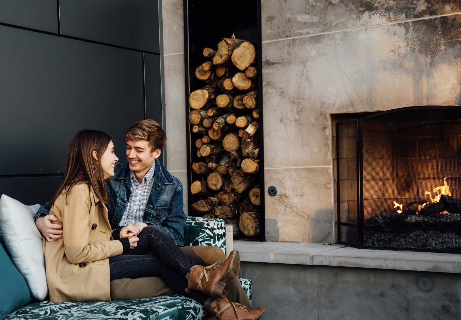 Engaged couple on hotel rooftop in downtown Nashville sitting at fireplace cuddling