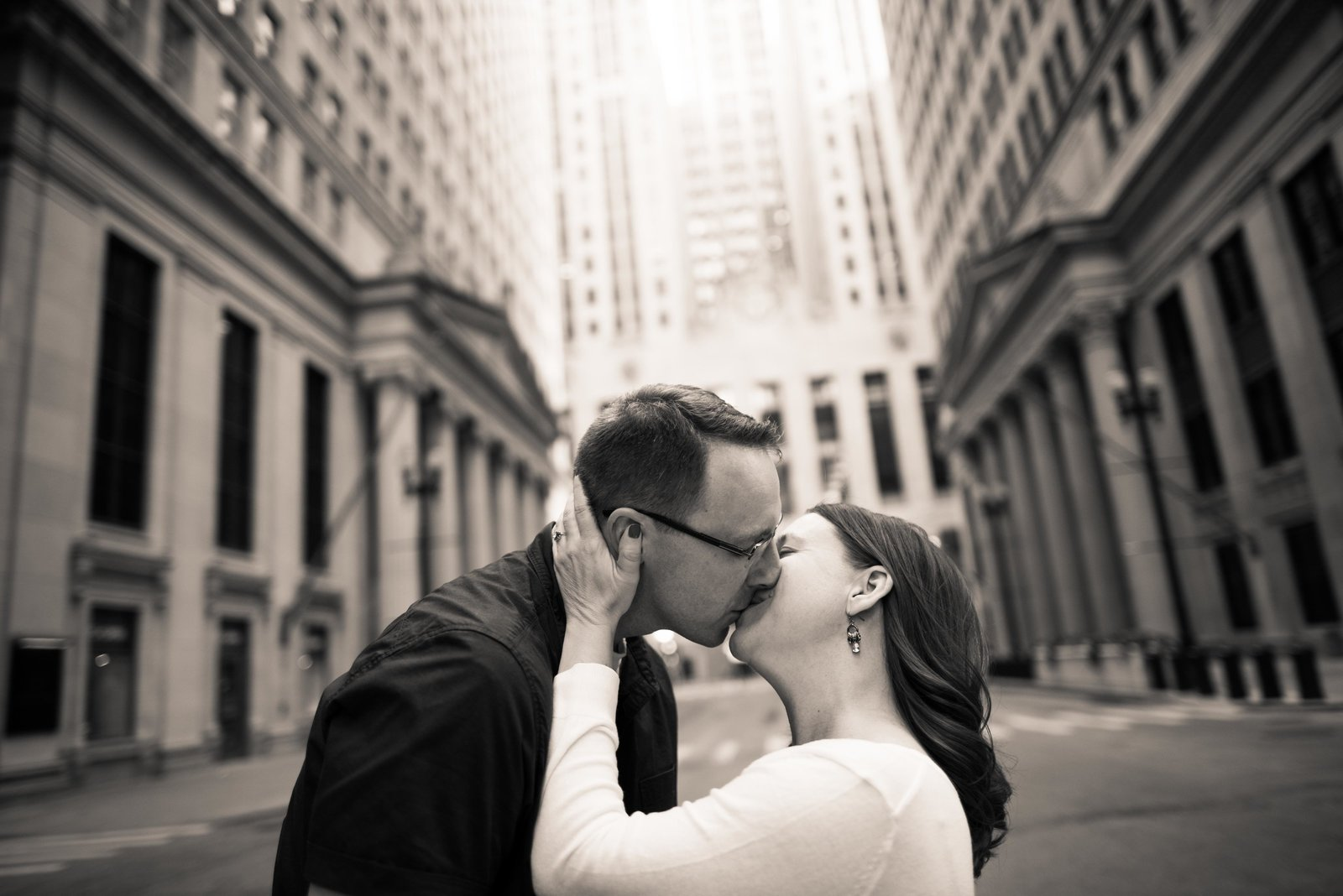 Couple, engaged, kiss on Dearborn in the Loop in Chicago.