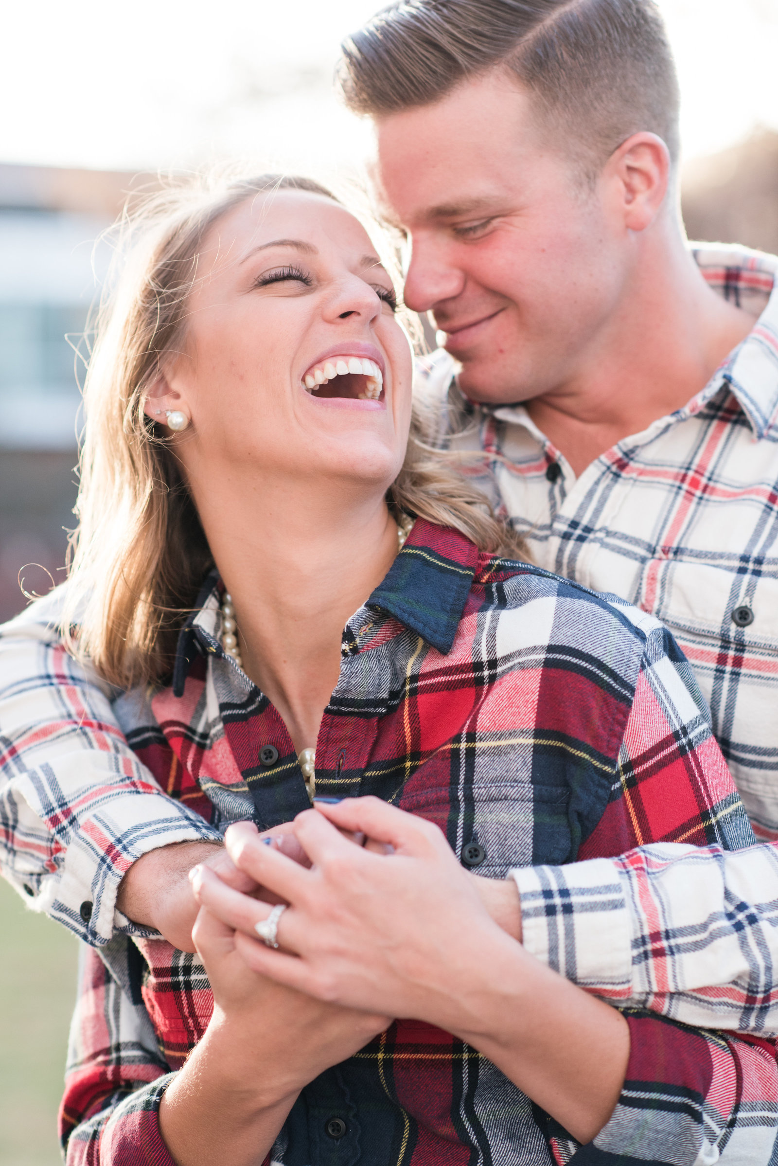 a young couple snuggled into one another wearing plaid at the American  Tobacco Campus