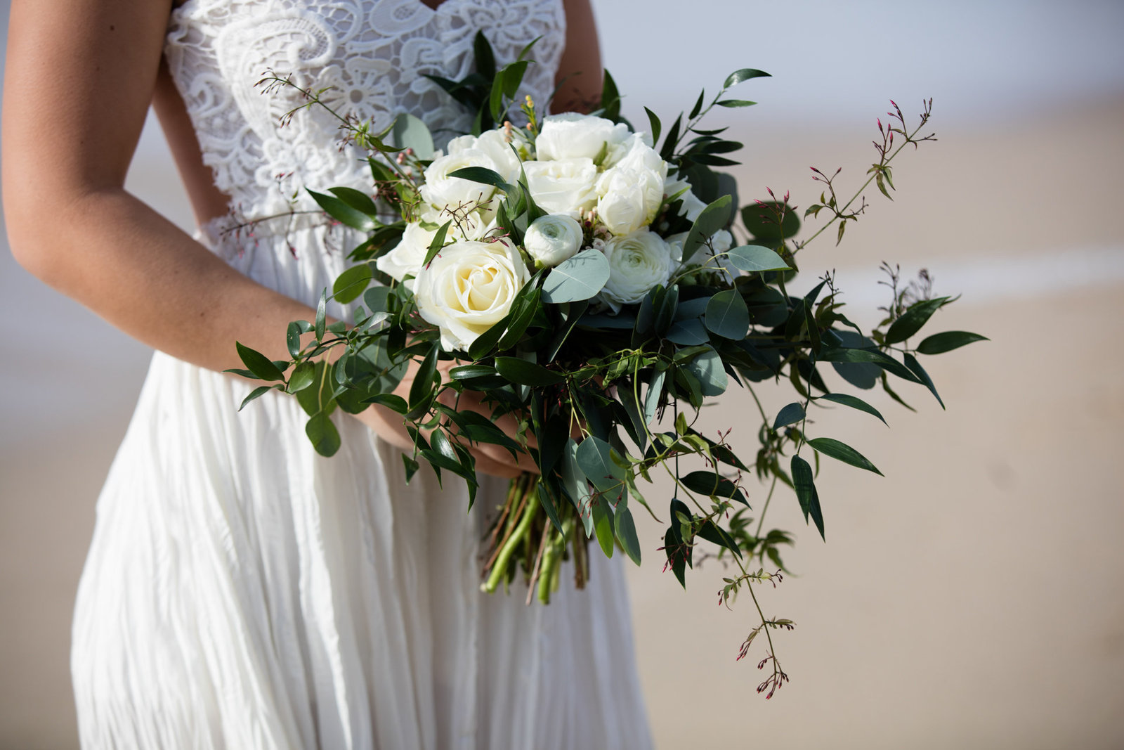 The bouquet is held by the bride in stunning beach engagement session