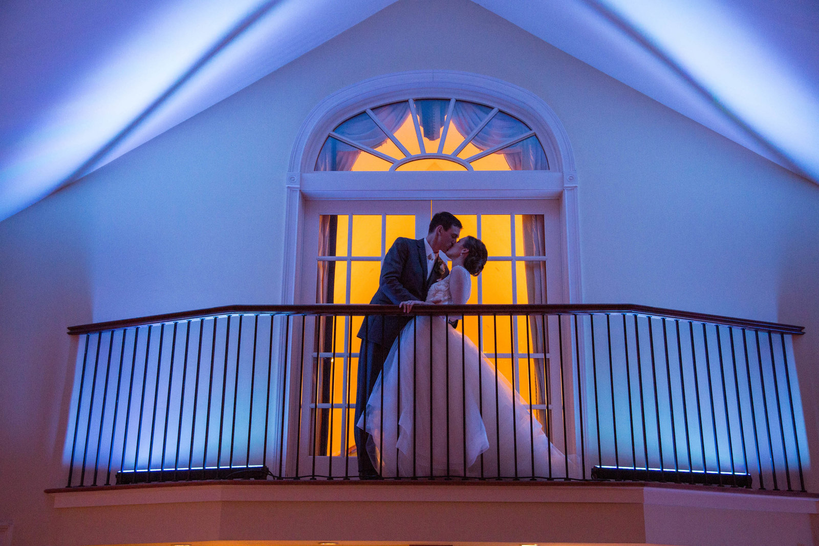 bride and groom kissing on balcony at The Riverhouse