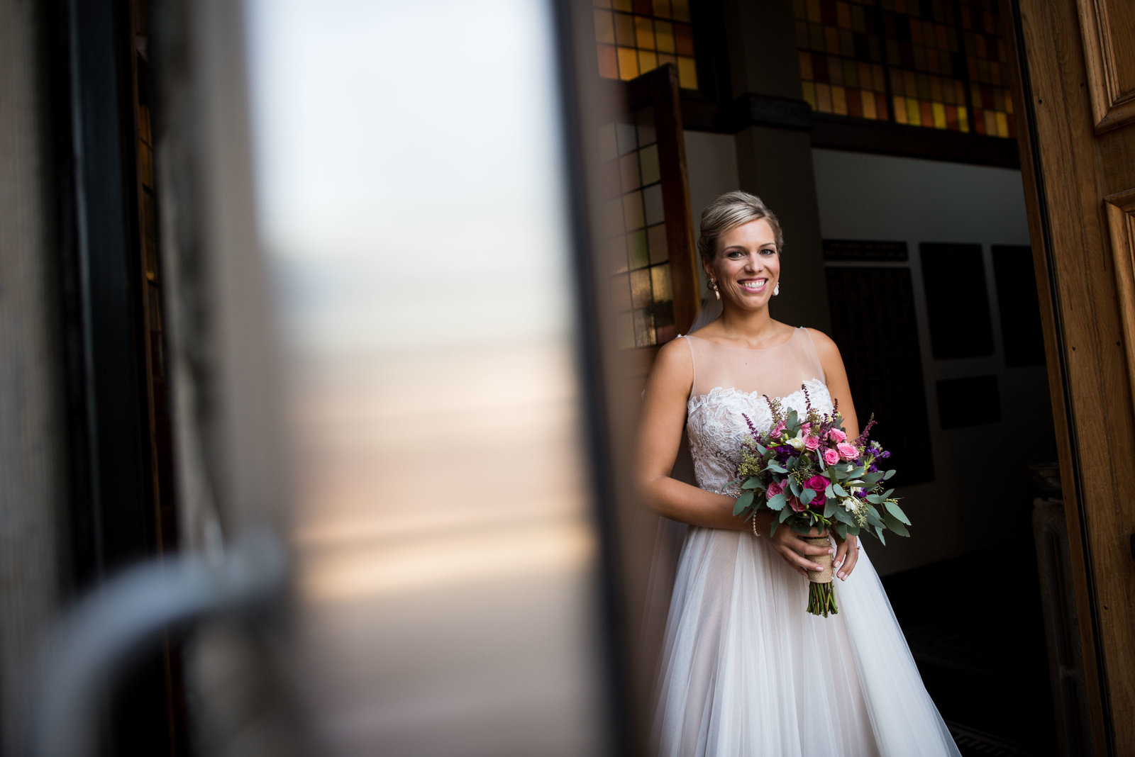 Bride poses at church door with bouquet after Chicago wedding ceremony.