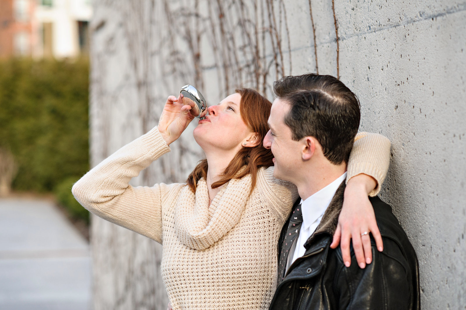A engaged couple sip whiskey to warm them up during their fall engagement session.