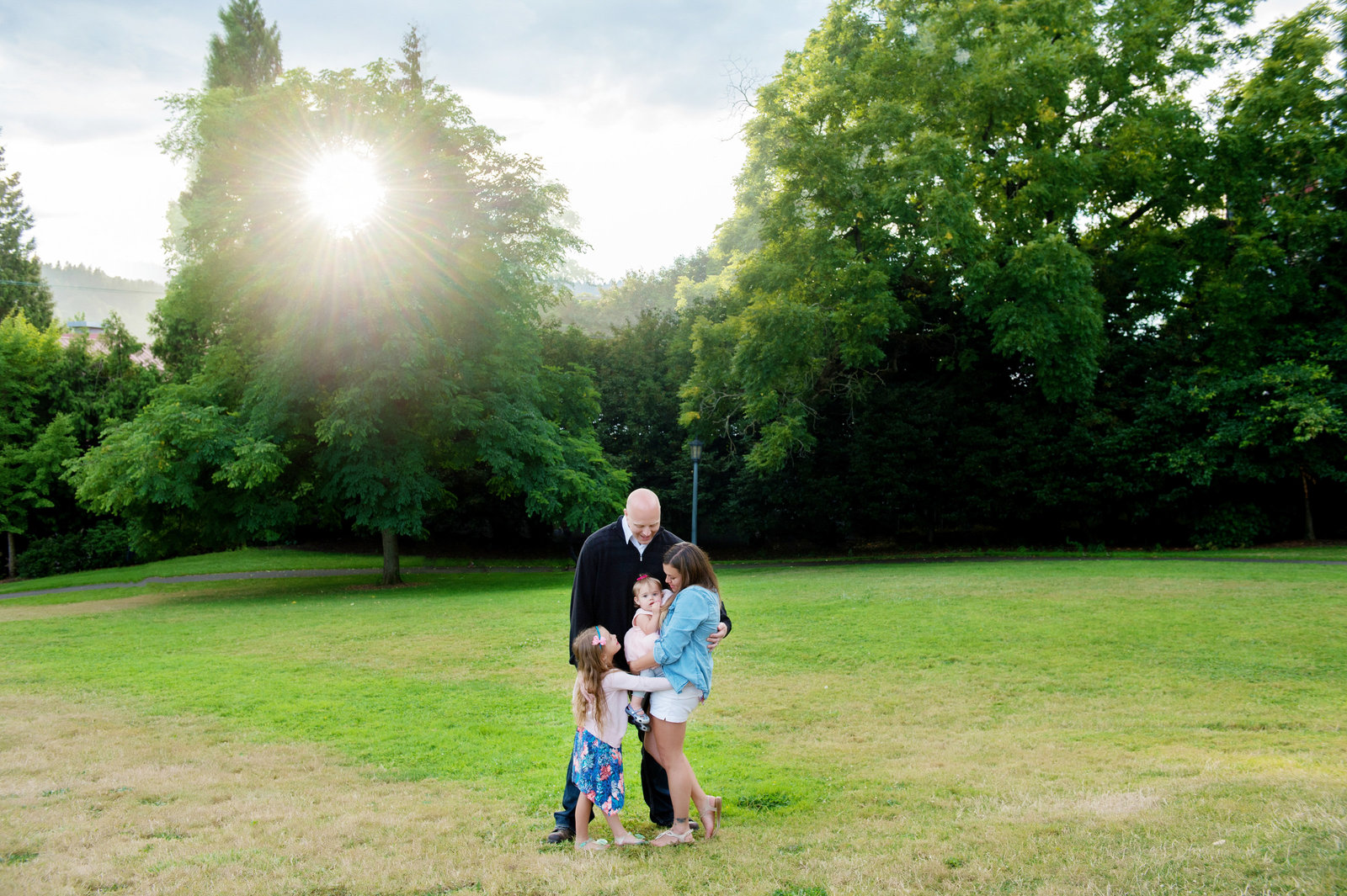 a family hugs together as the sun shines through the trees at cathedral park