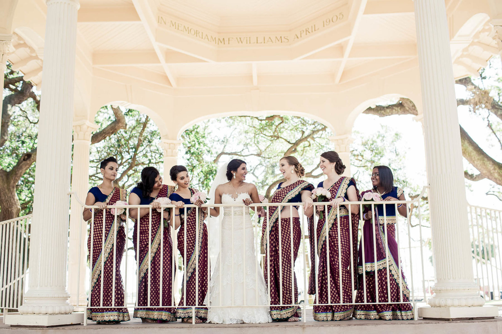 Bride poses with bridesmaids at gazebo of White Point Garden, South Carolina