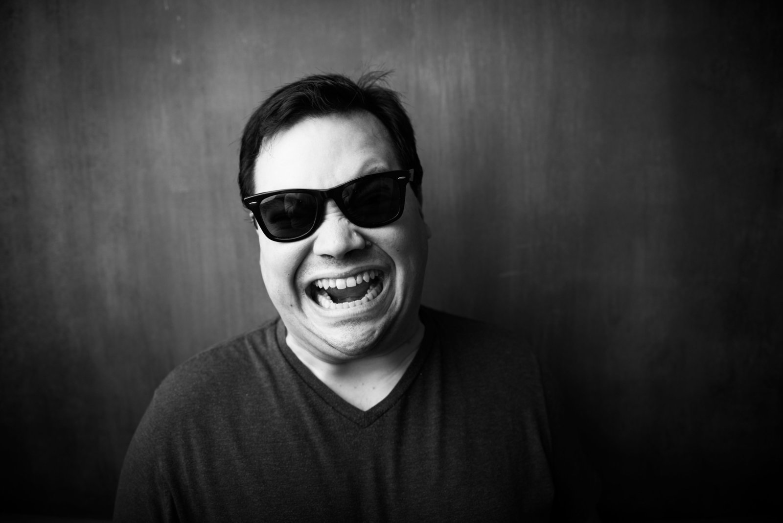 Studio portrait, black and white, man screaming with sunglasses.