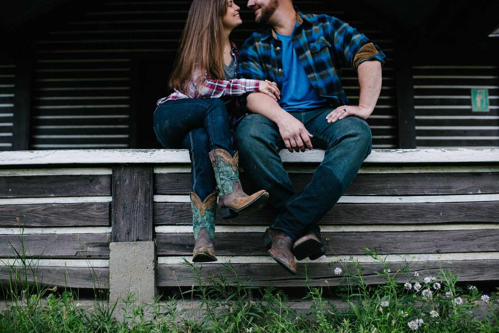 Brady Run couple sitting on rustic log cabin