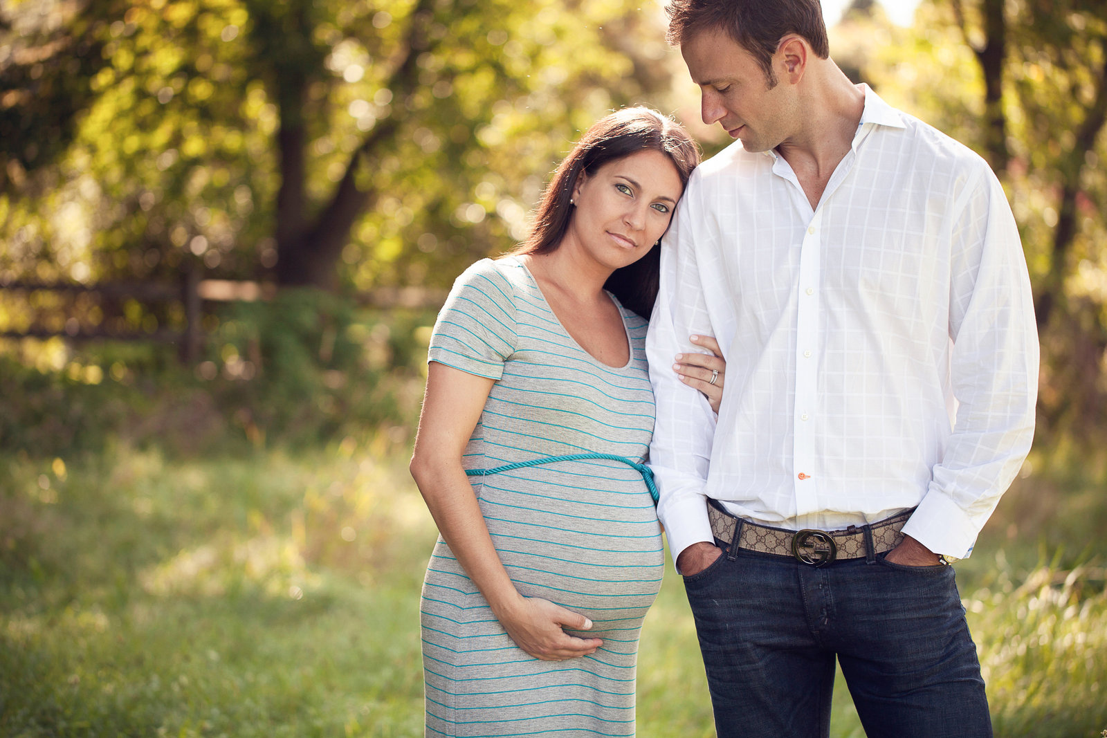 Man looks at pregnant wife in blue dress