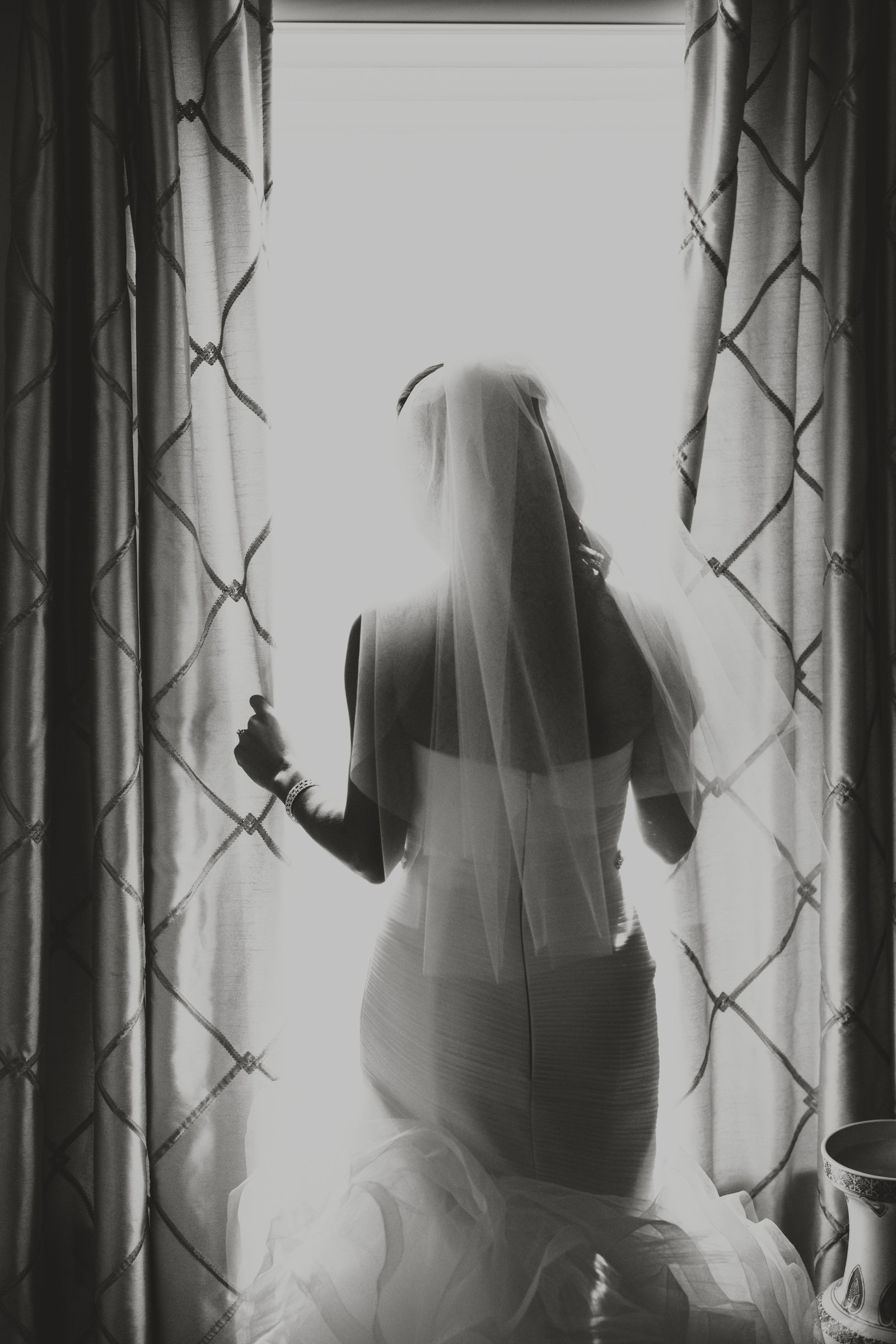 a bride peeks out the window on her wedding day in black and white