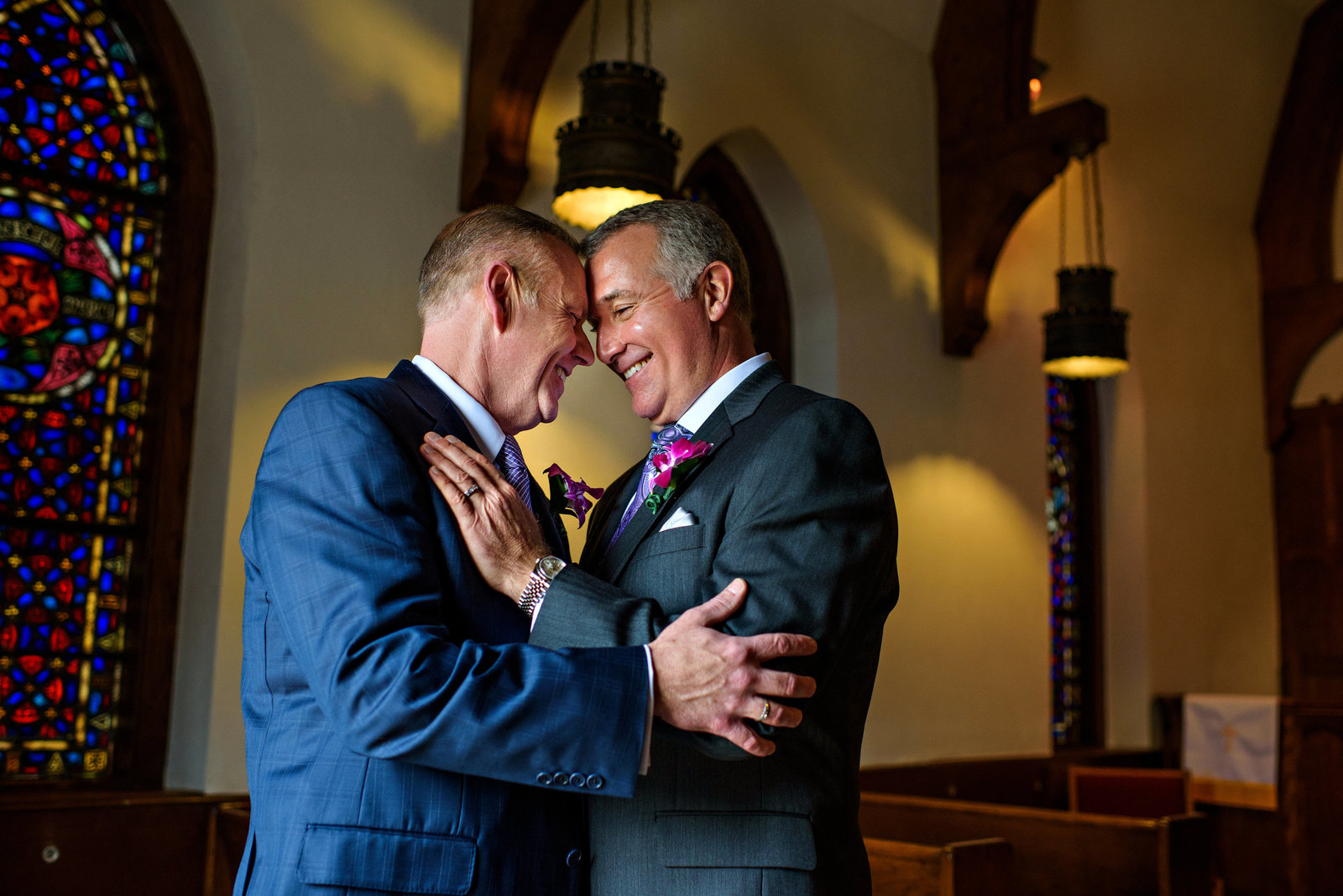 Two grooms share in the excitement of their same sex wedding.