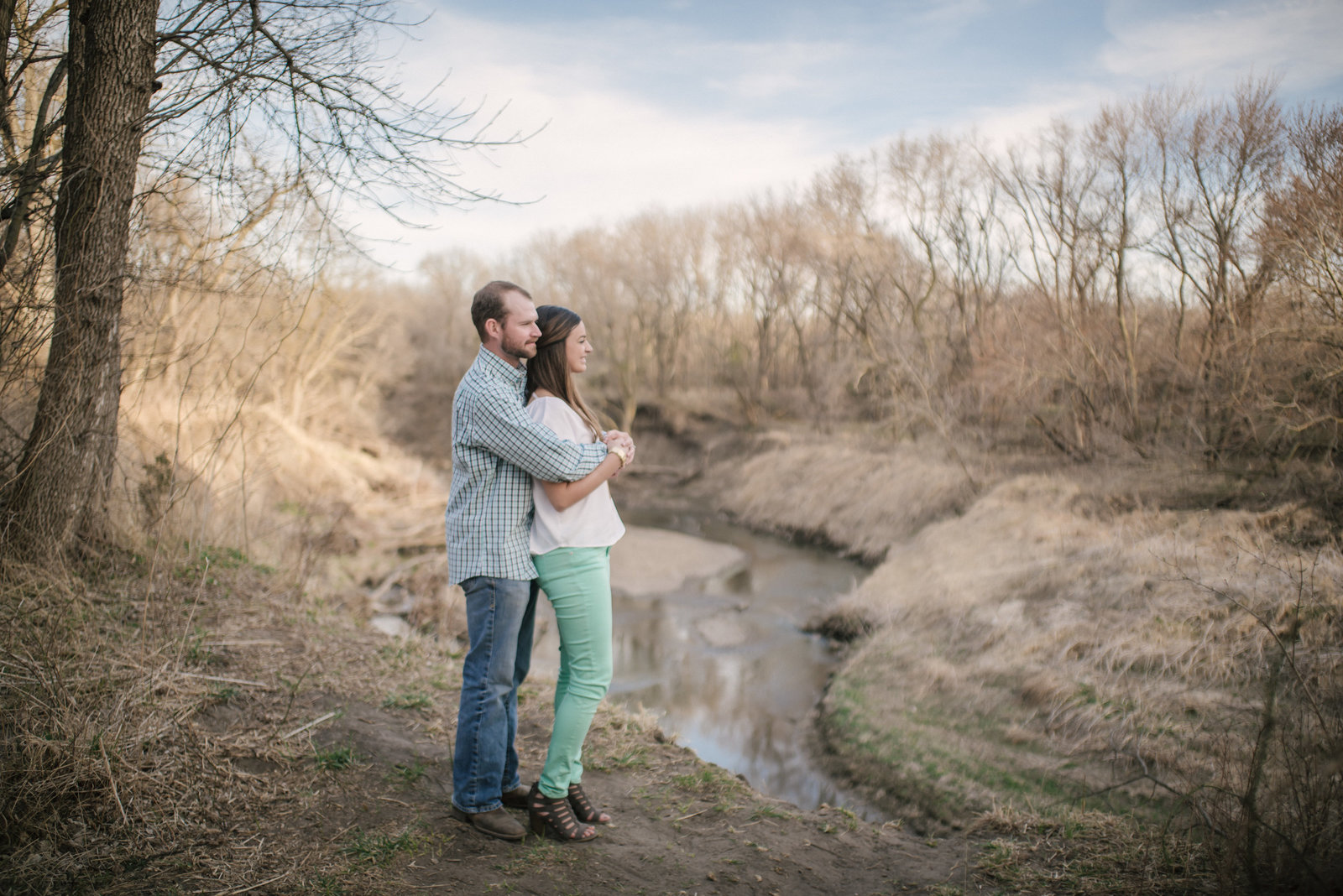 couple overlooking creek at engagement shoot