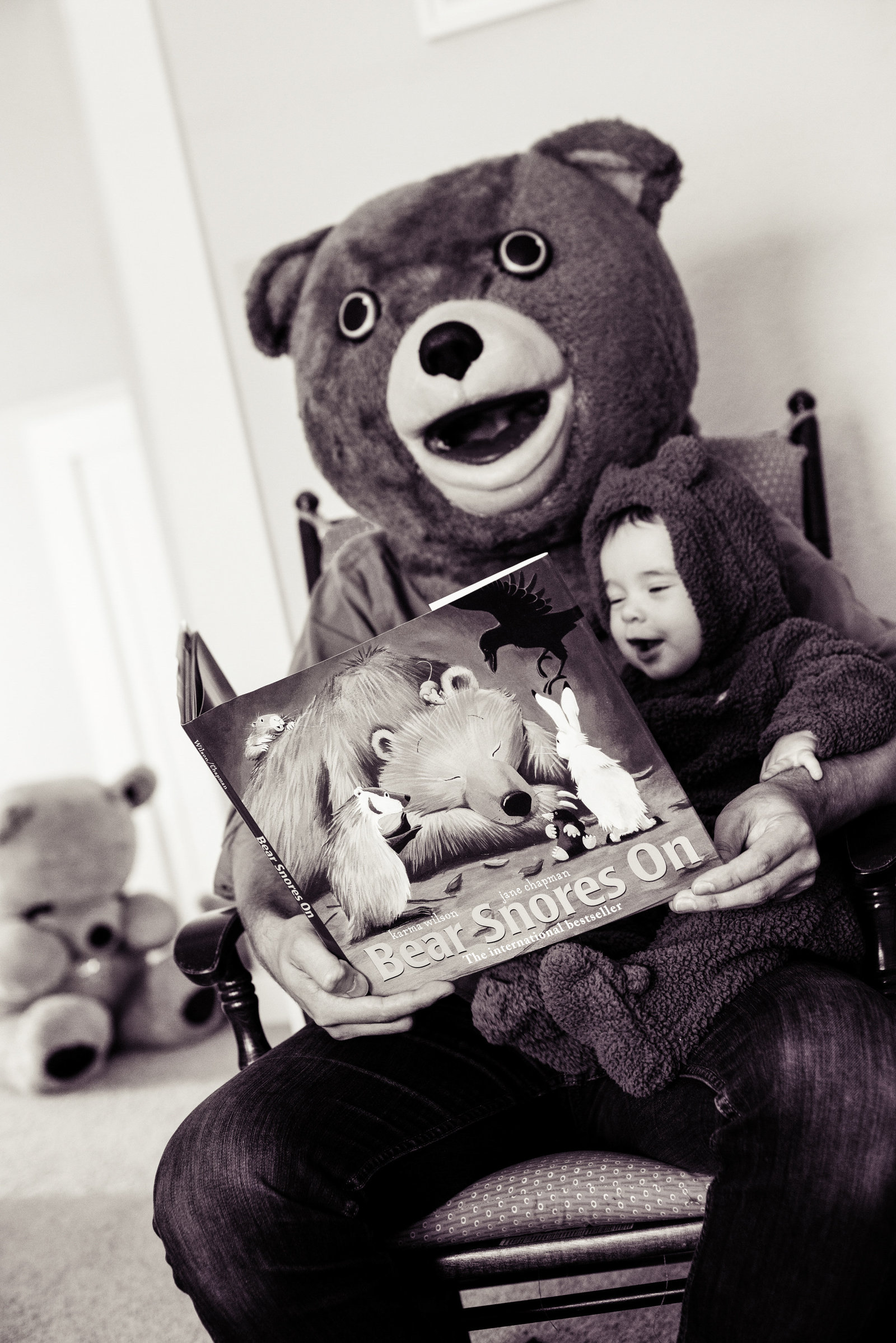 a dad dressed in a bear costume reads a bear book to his son also wearing a bear costume
