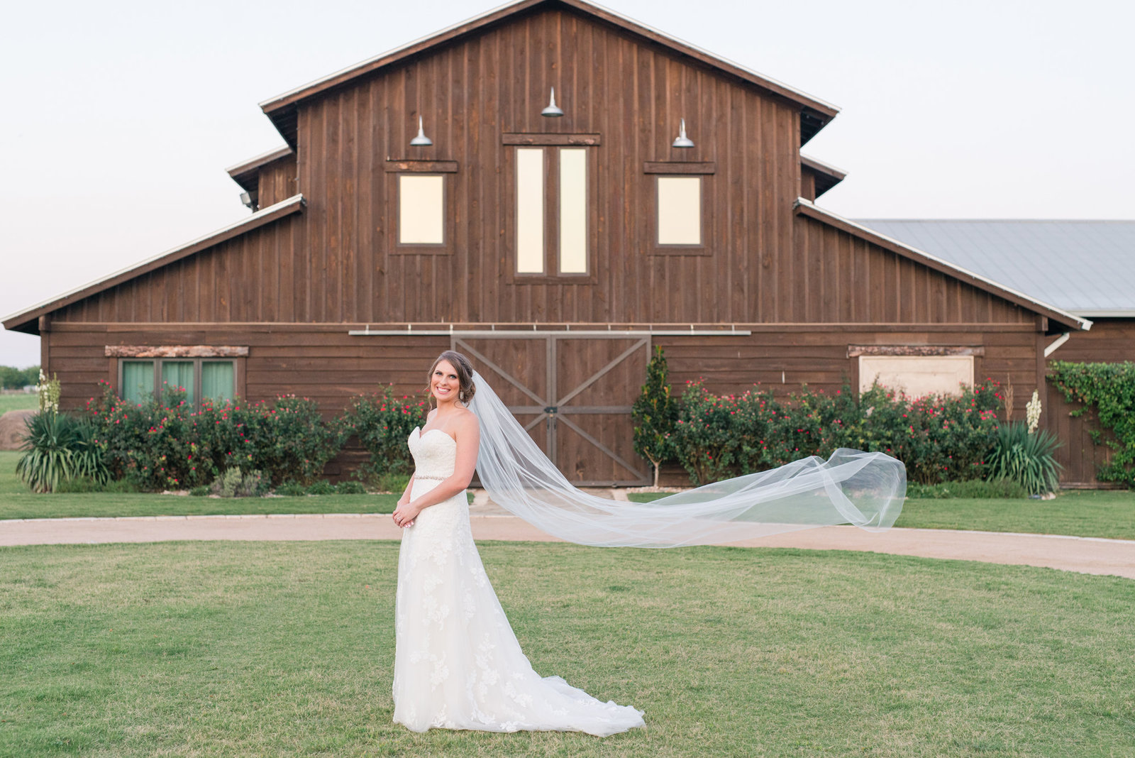 Bride smiles as her veil is caught by the wind in front of Lone Oak Barn in Round Rock