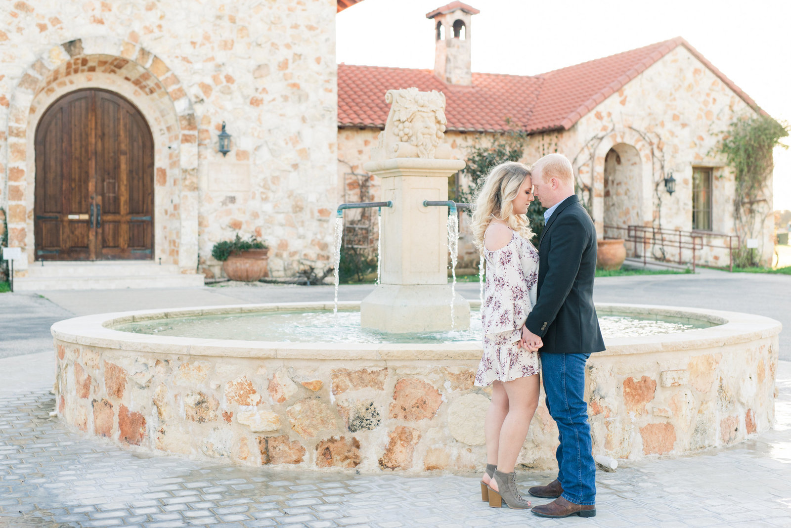 Bride in white and purple floral dress holds hand of groom in suit jacket in front of fountain at The Vineyard at Florence