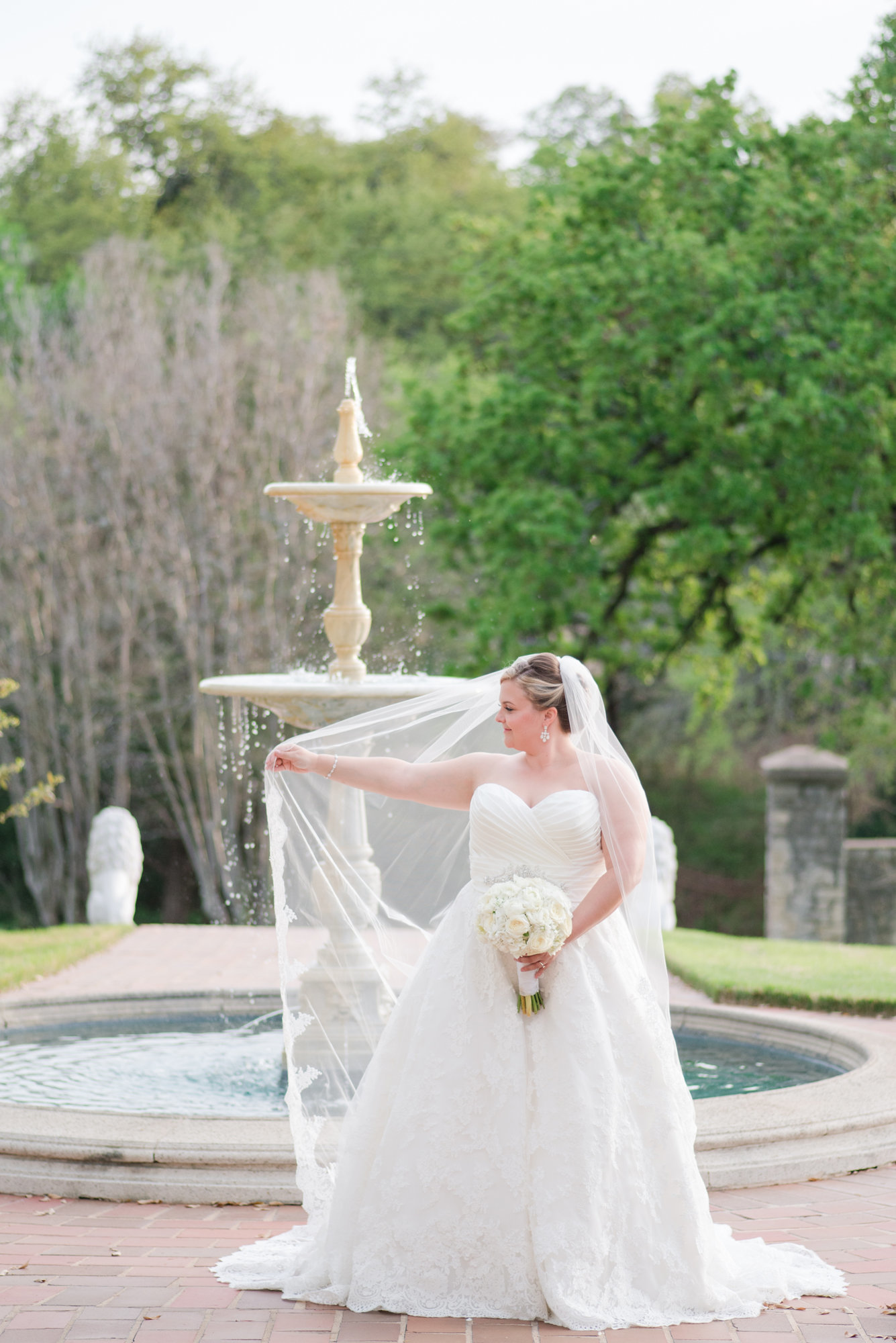 Bride twirls her wedding veil in front of fountain of Commodore Perry Estate