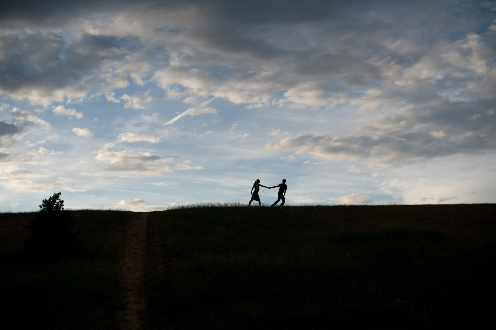 a couple holding hands silhouetted on top of a hill in denver with pretty blue sky