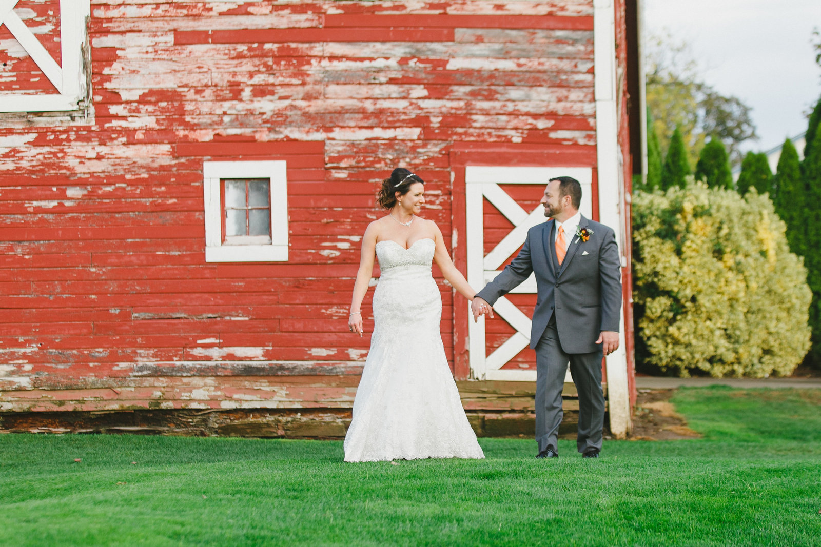 photo of bride and groom walking in front of a barn at Langdon Farms | Susie Moreno Photography