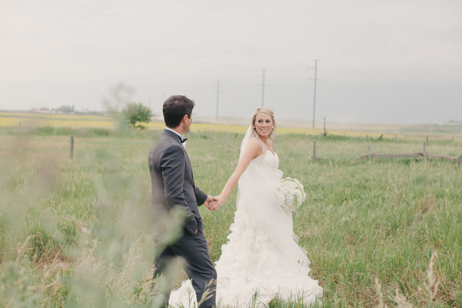 Bride and Groom walk through field