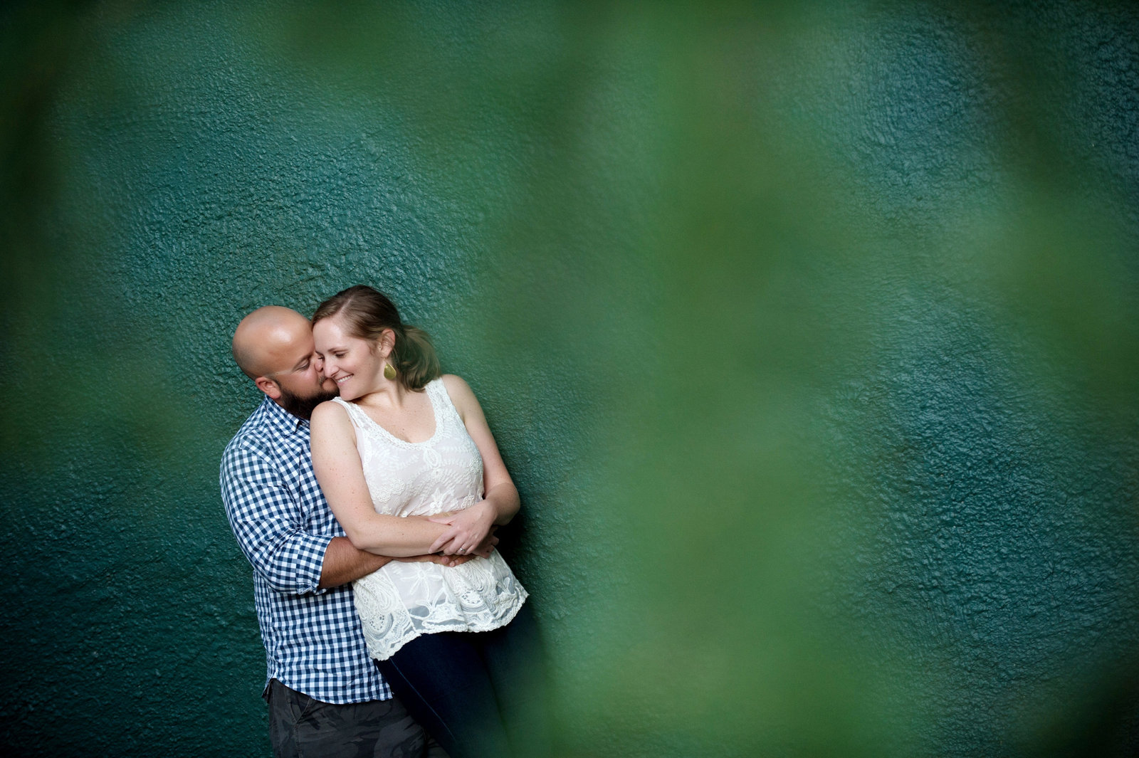 a couple embrace against a green wall with green leaves in the foreground