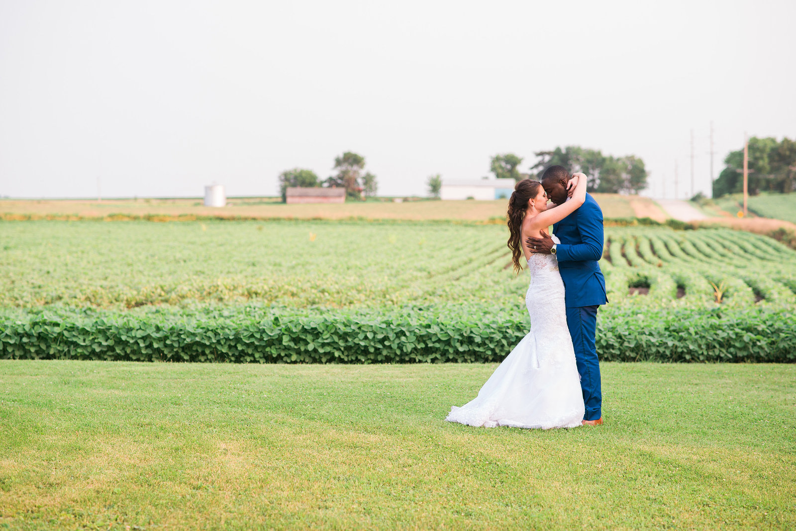 Midwest Iowa Wedding Photographer couple in bean fields and gravel road at sunset