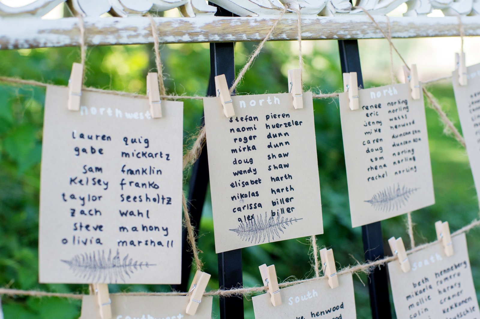 wedding reception dinner seating chart clipped to a frame with tiny clothespins