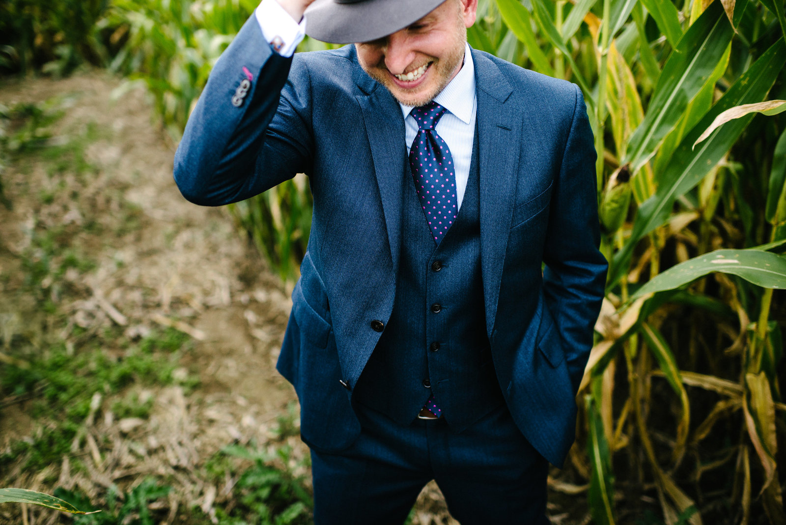Columbiana OH groom in navy tux and fedora standing in corn field