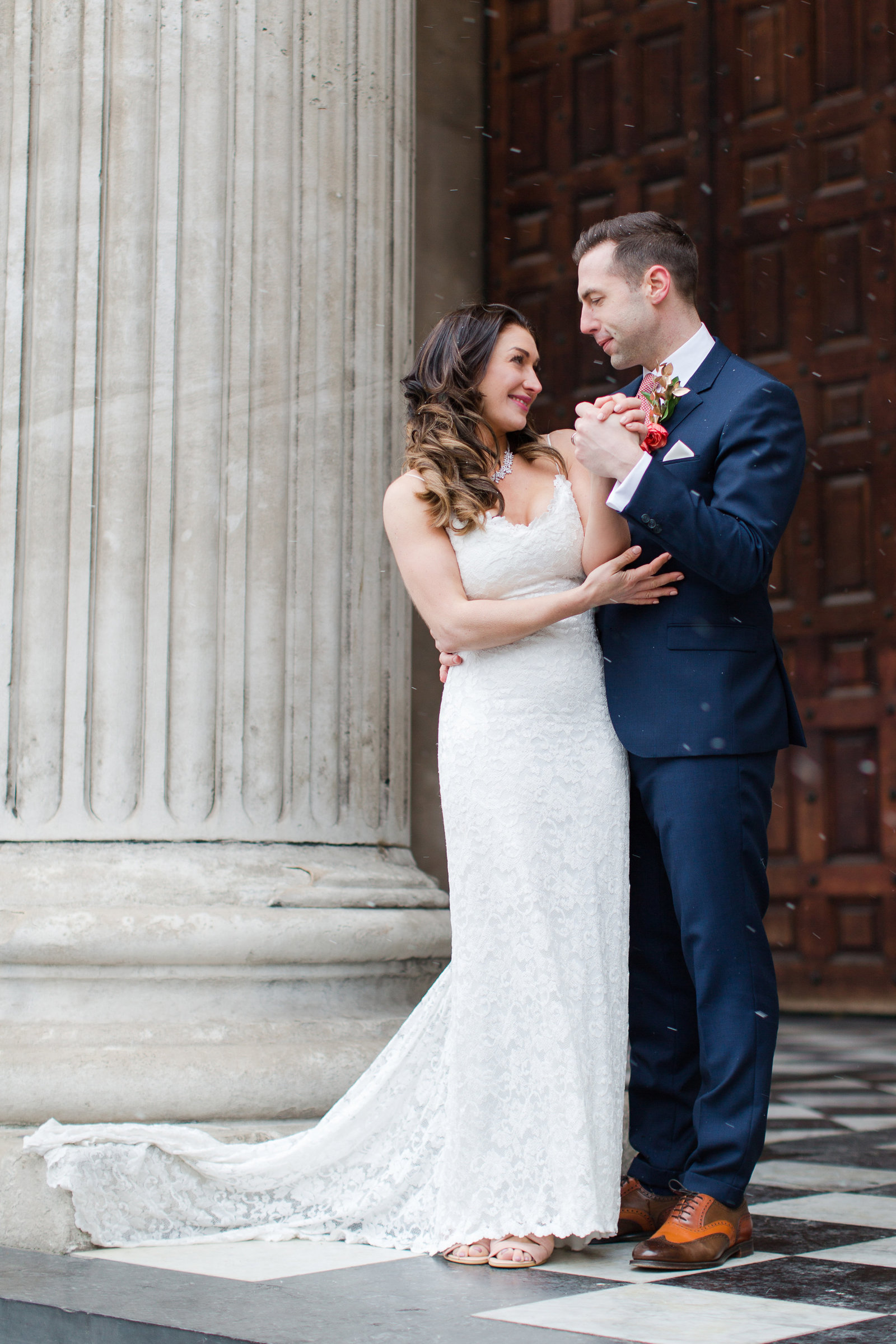 Bride and groom hold hands and stare into each others eyes intimately at this snowy winter wedding at St Paul's cathedral in London