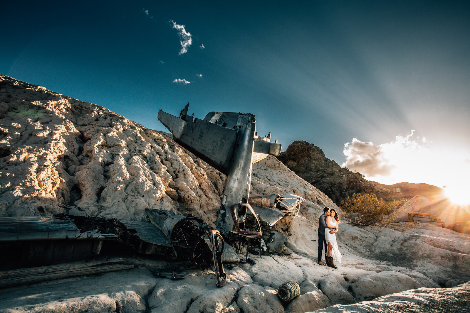 groom hugs bride near airplane wreck at nelsons ghost town