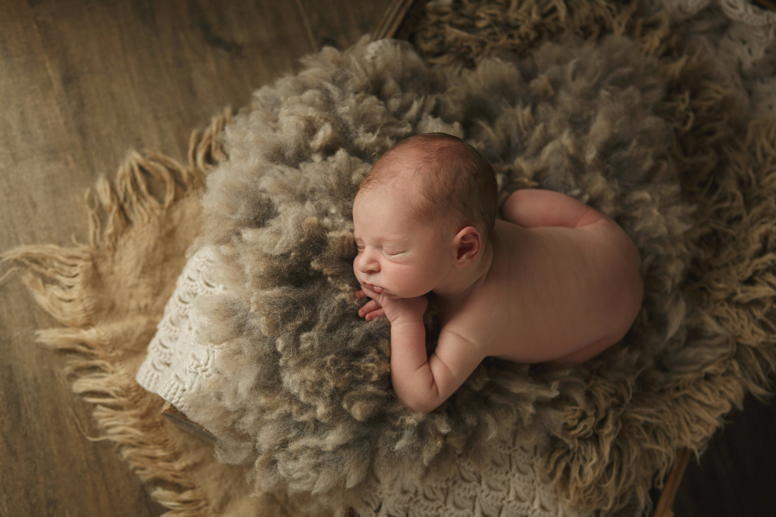 baby boy newborn sleeping in wool and burlap in a barnwood crate on wood backdrop hudson valley ny photographer