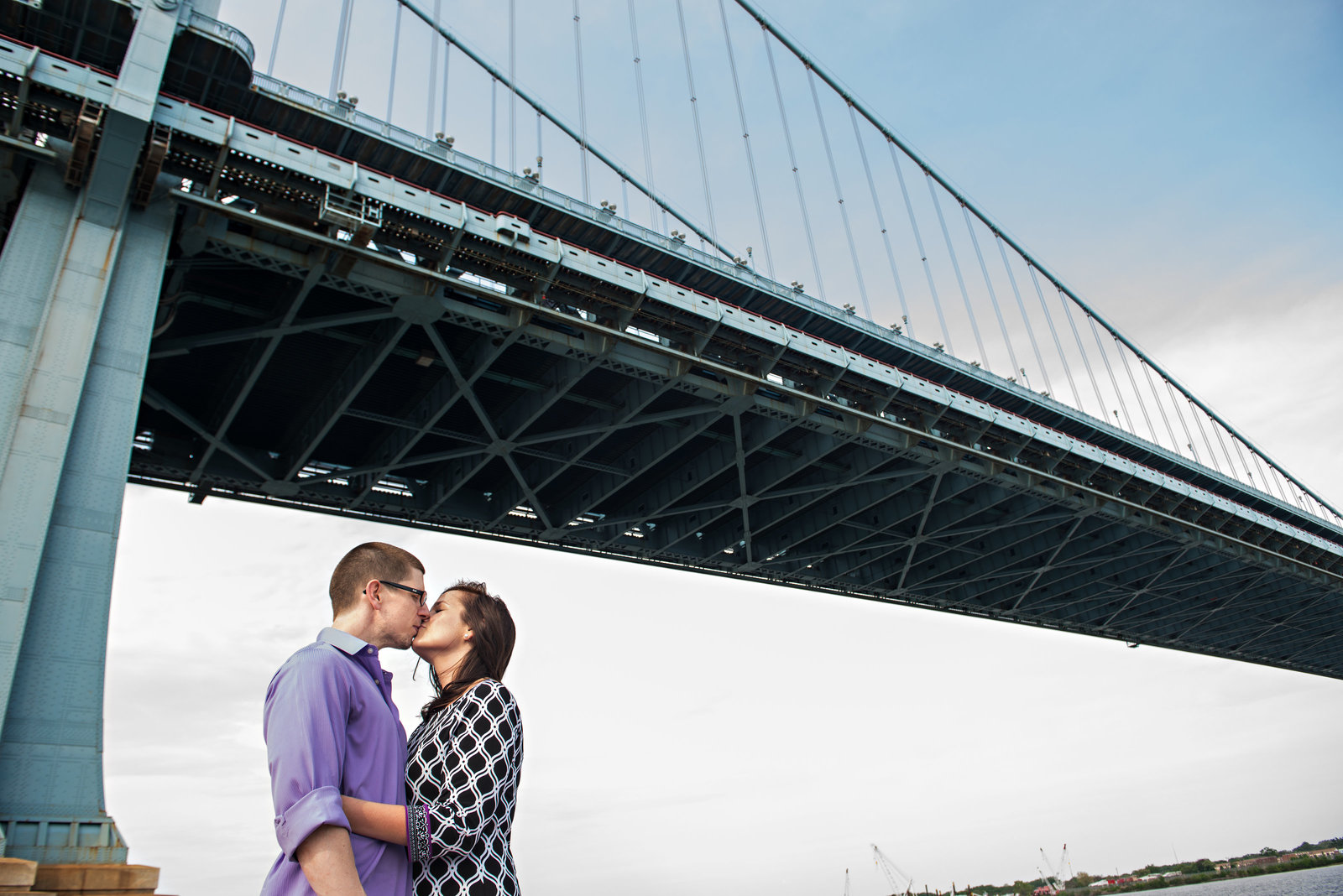 A couple kiss under the ben franklin bridge in philadelphia.