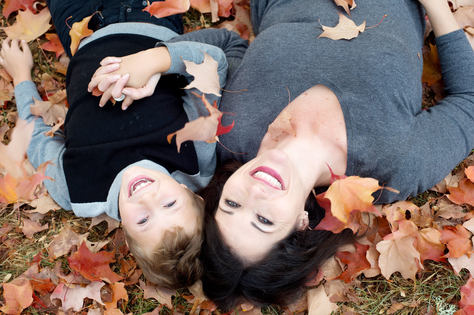 a mom and son lay in some fallen colorful leaves at hoyt arboretum