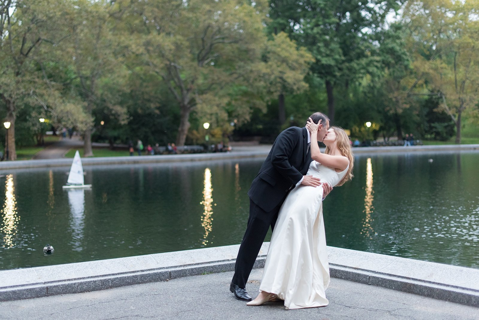 Groom dipping and Kissing Bride in front of pond with little boats at Conservatory Water in Central Park, New York City Photo