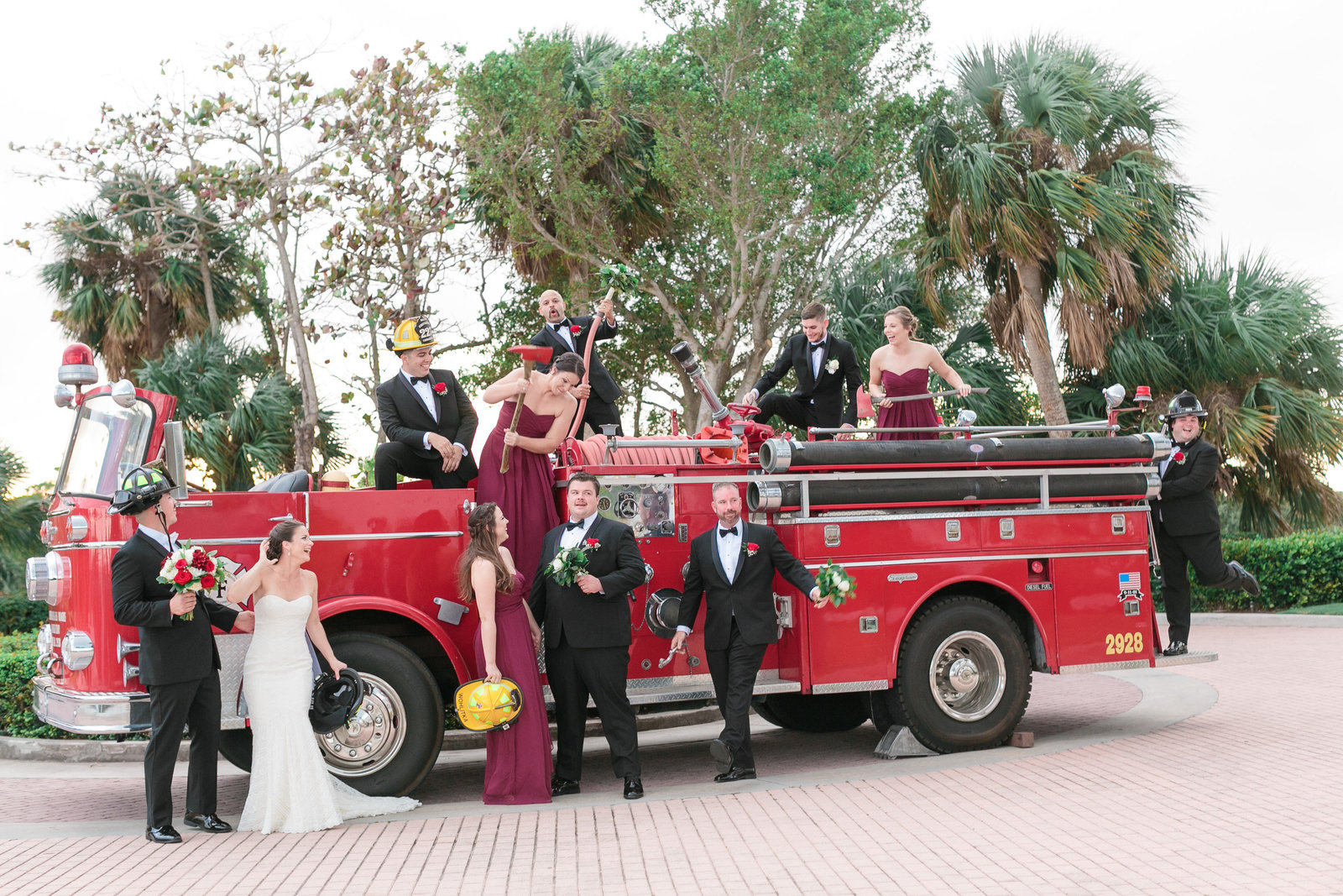 Bride, groom, bridesmaids, and groomsman  in a photo with a firetruck at mansion of tuckahoe