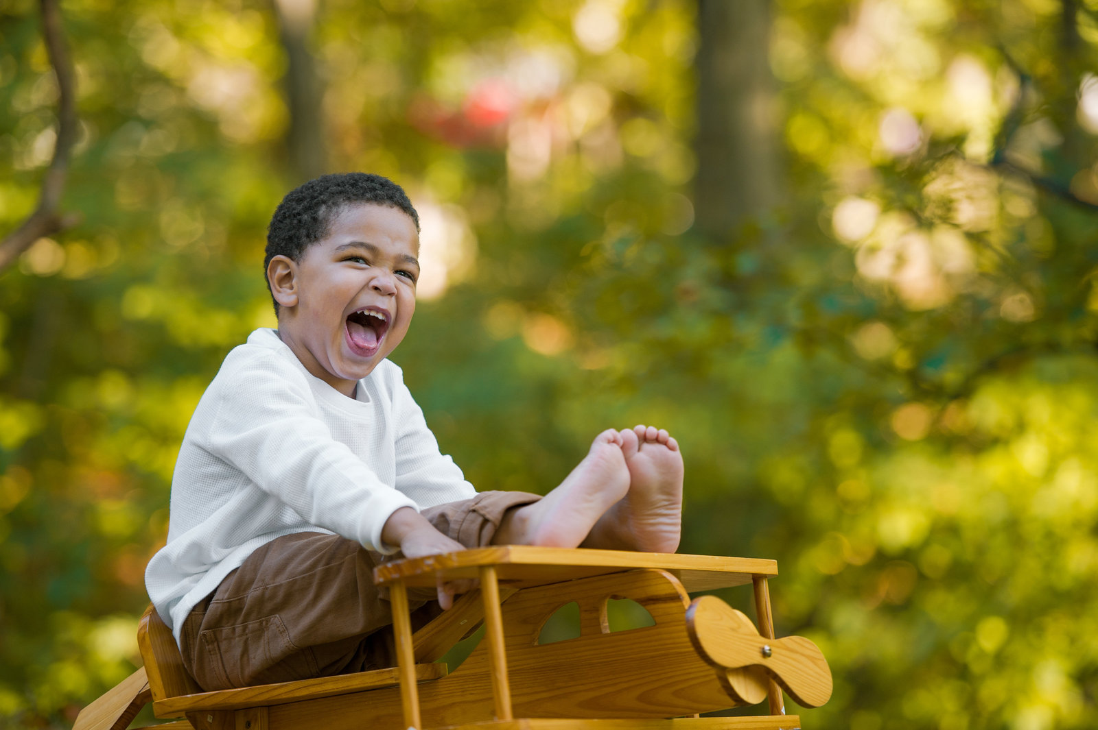laughing boy sitting on wood airplane rocker