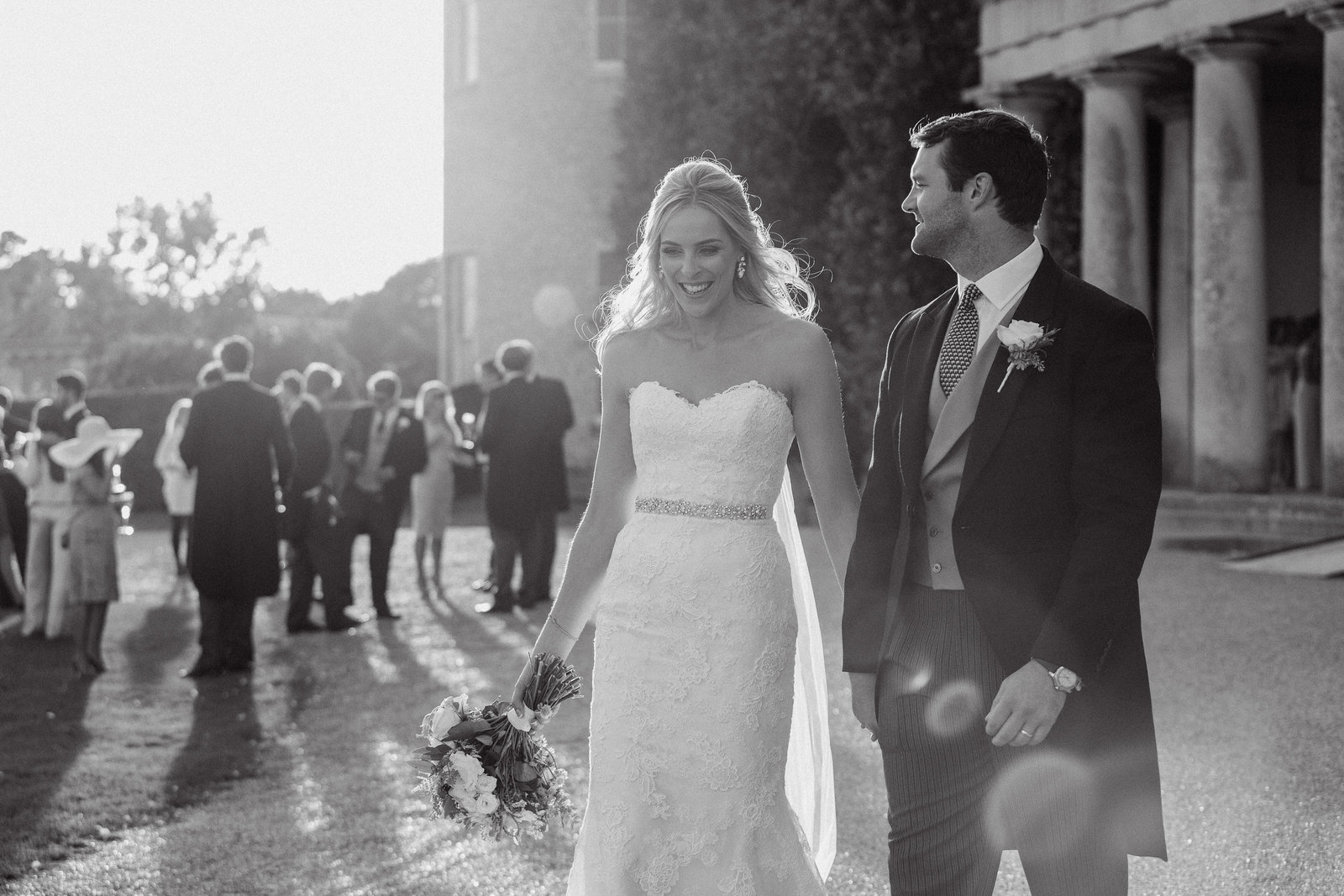 Beautiful black and white photo showing the bride and groom walking with Goodwood House and guests in the background on their wedding day during golden hour with sun flare and captured by the talented west sussex wedding photographer Nicci at Adorlee