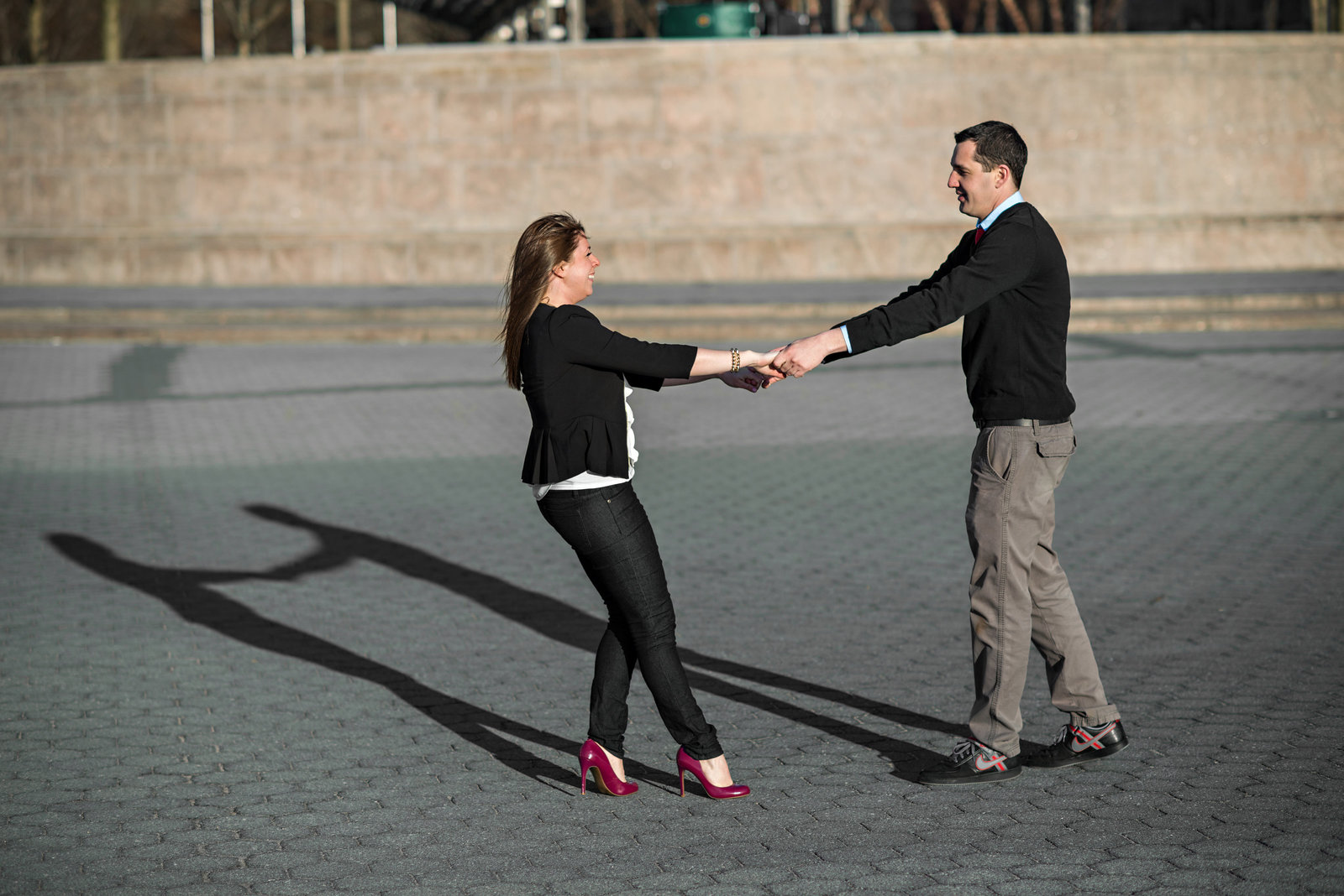 A man and woman dance in the park in downtown NYC.