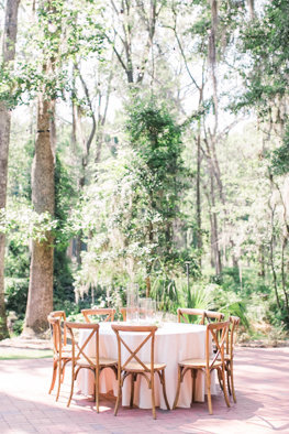 Round table with wooden chairs sitting in front of trees with Spanish Moss