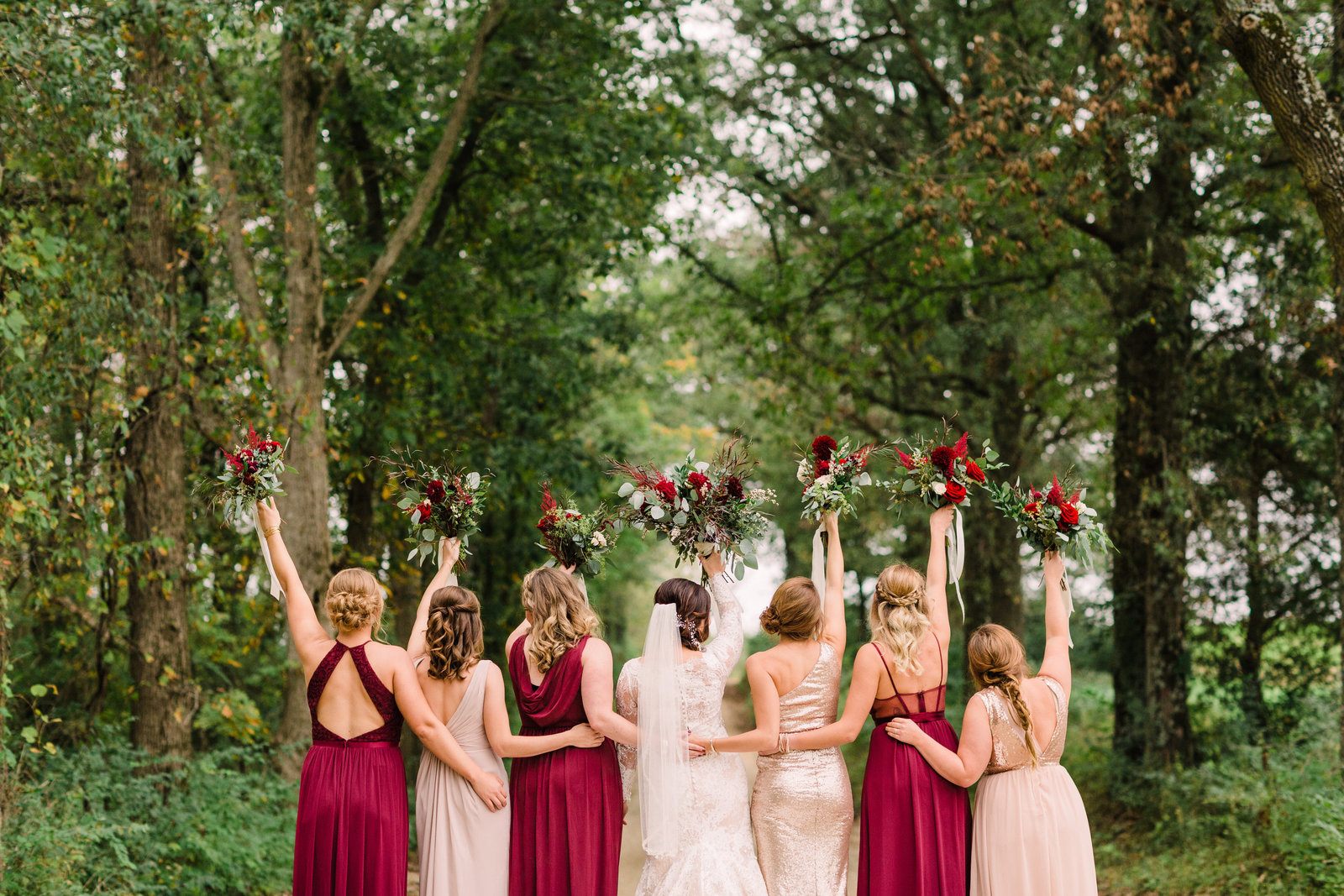 Bridesmaid pose with flowers in the air for this Rustic yet elegant wedding at Three Barn Farm with pops of burgundy and navy by Jackelynn Noel Photography