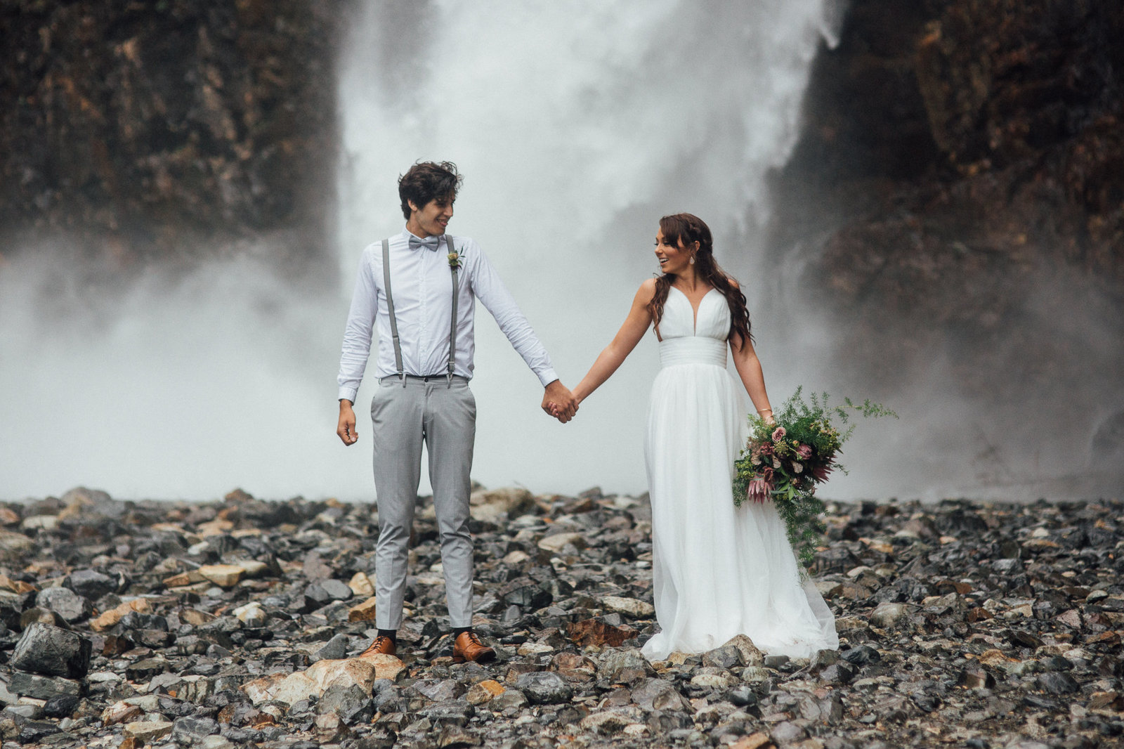 Elopement couple embrace in front of Franklin Falls in Seattle, WA