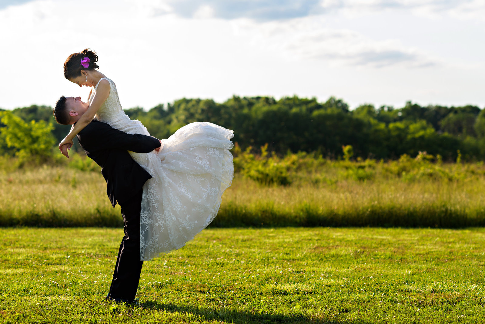 A groom spins his bride around in a field at their Pearl S Buck Estate Wedding.