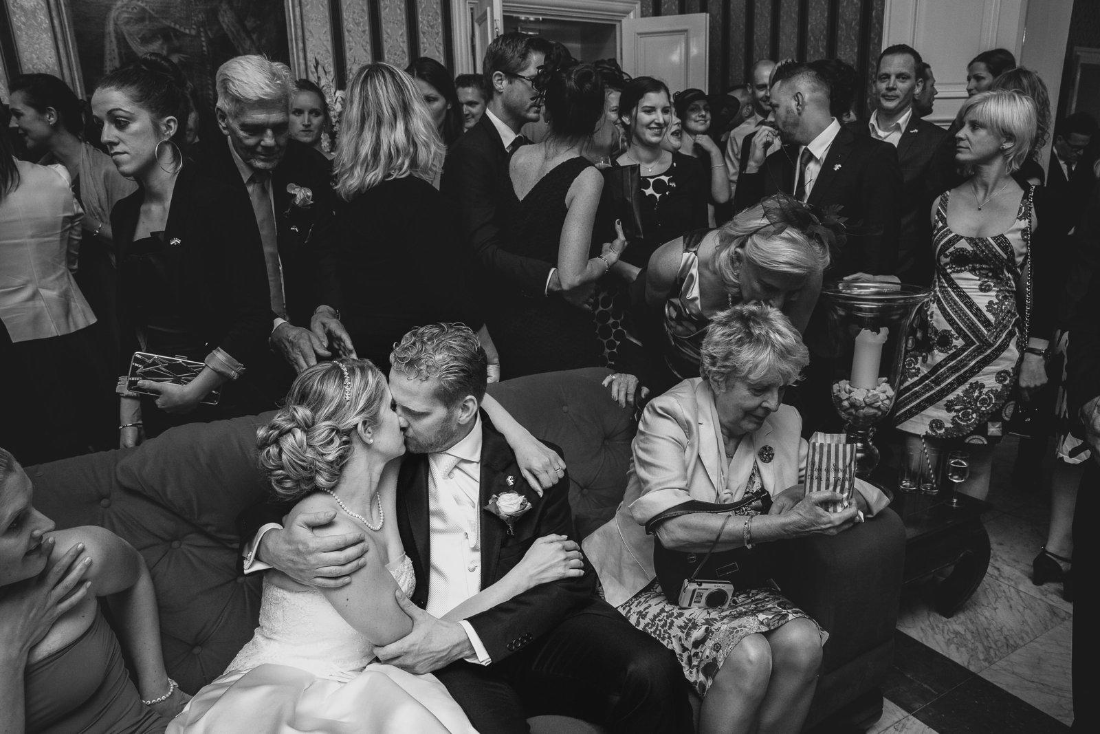Het bruidspaar verliest zichzelf helemaal in een kus in een zaal vol met mensen. Copyright Nanda Zee-Fritse | FOTOZEE