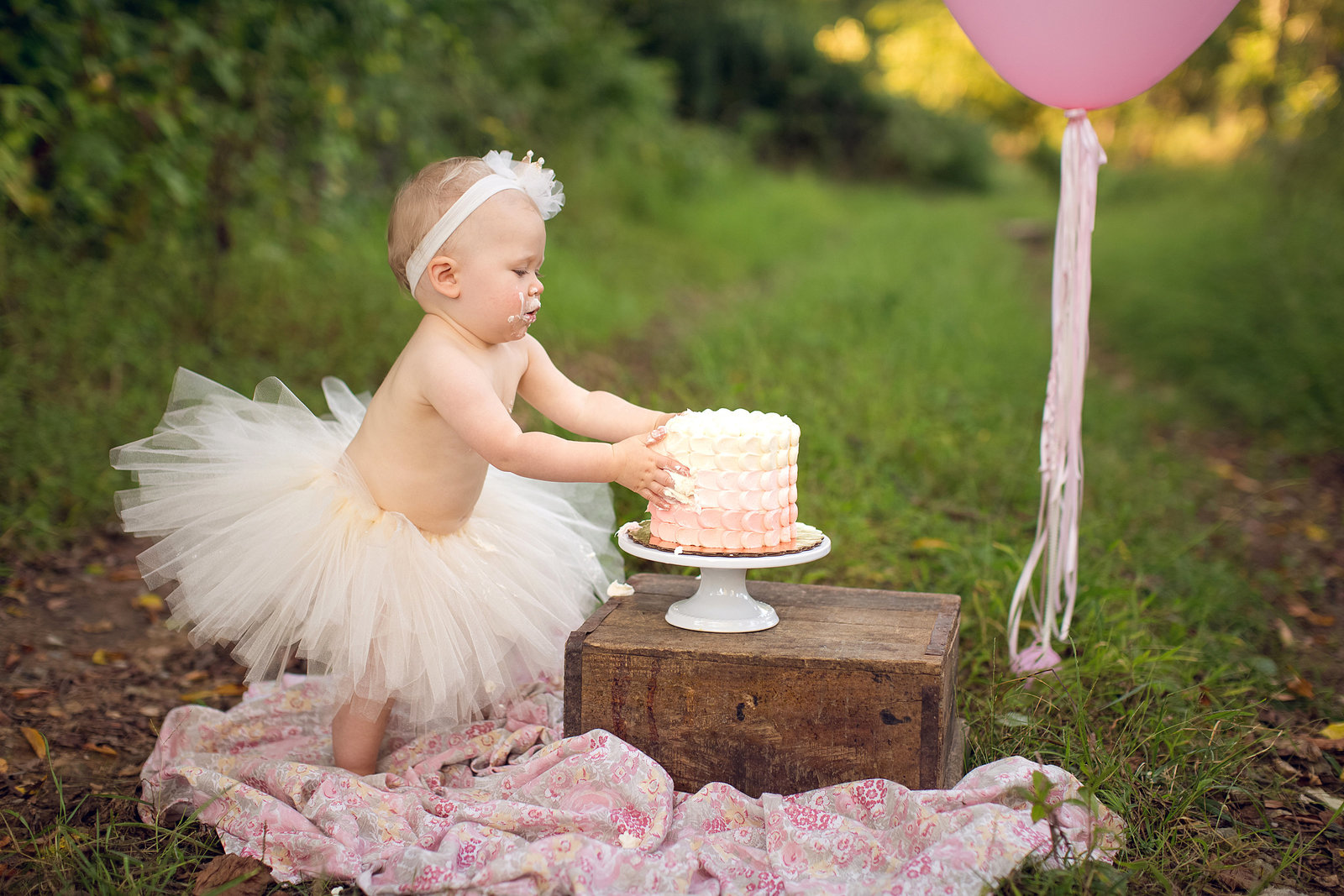 birthday girl in tutu reaches for cake