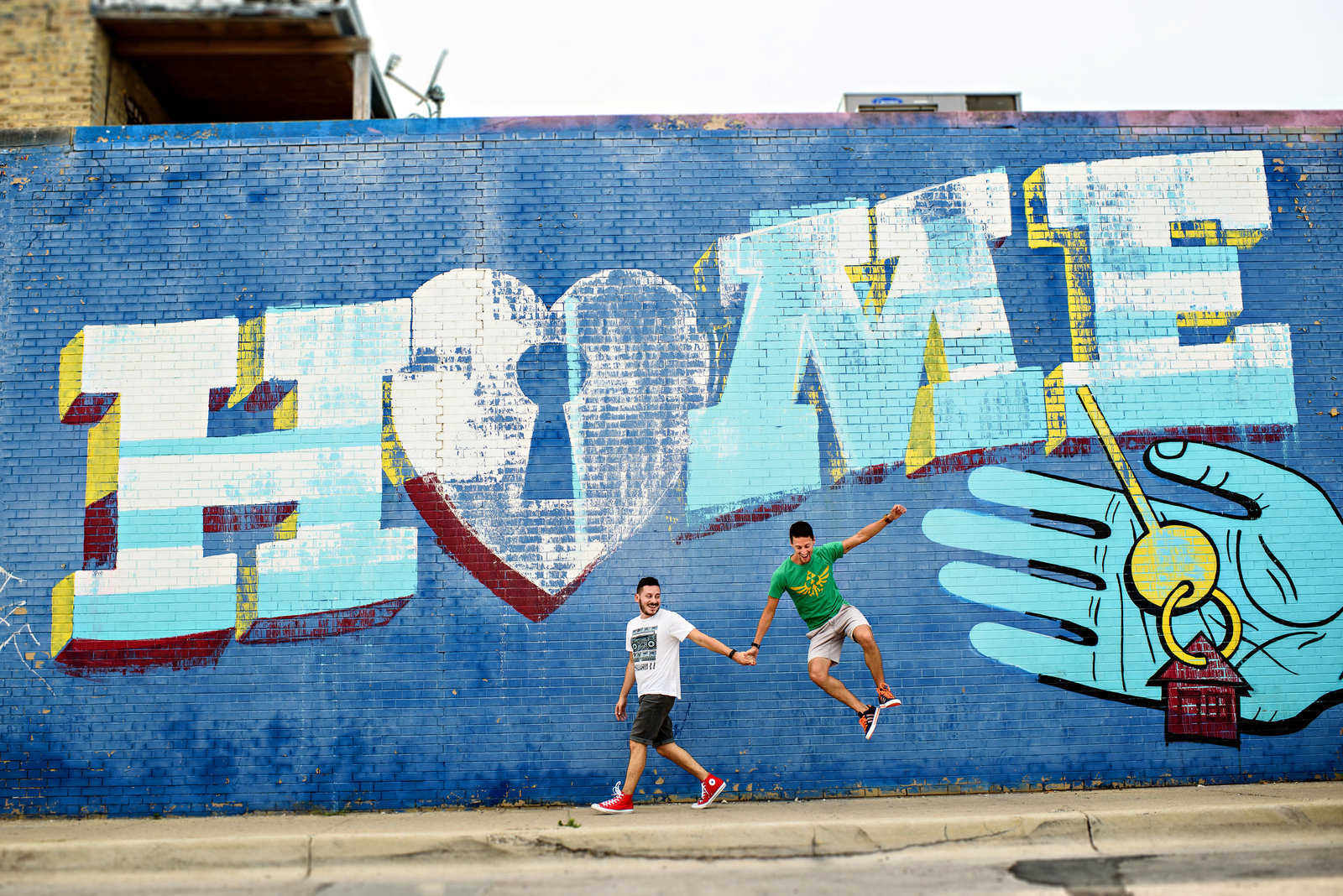 Two grooms jump for joy in front of a graffiti mural in Chicago.