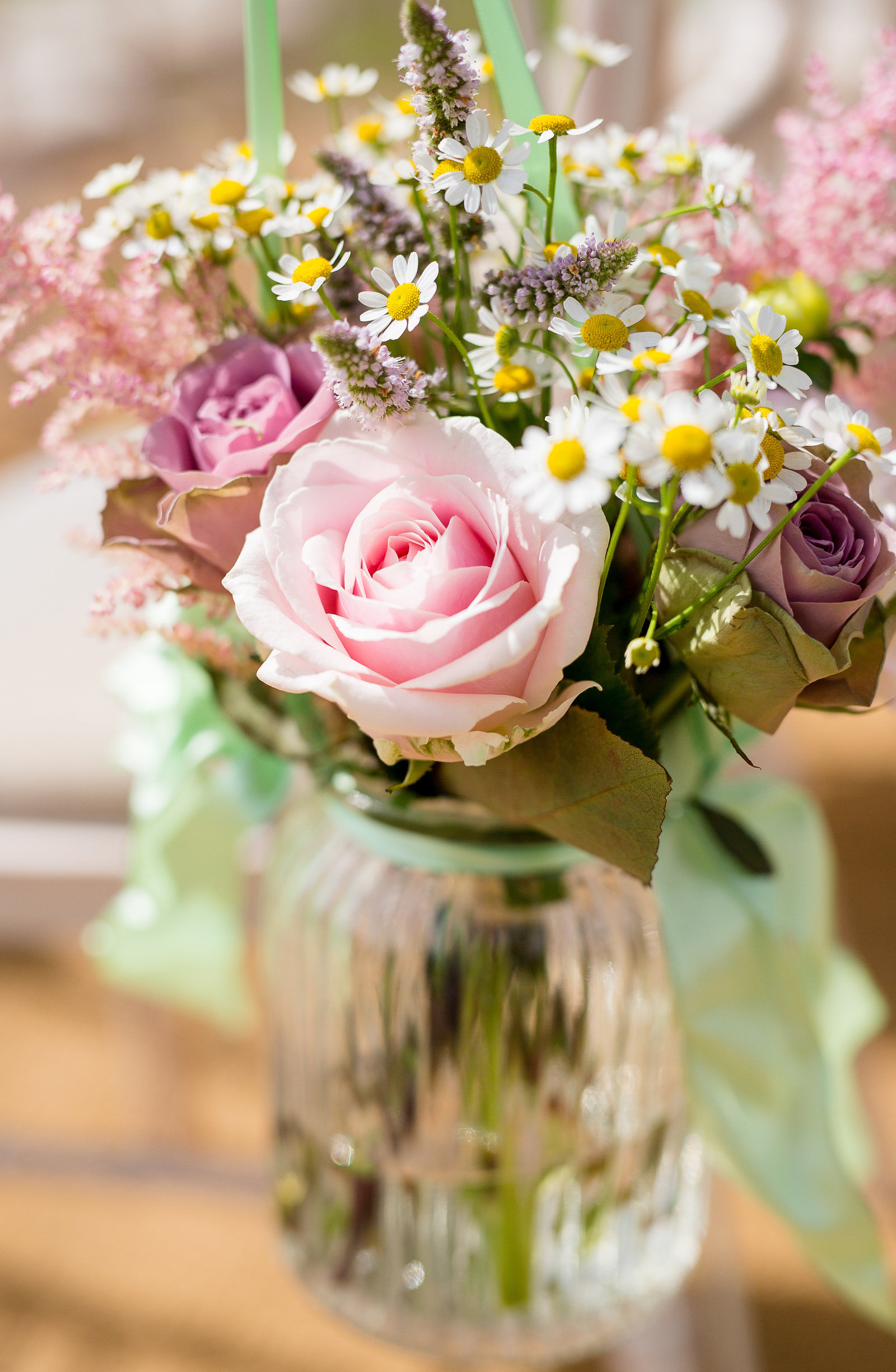On a budget beautiful roses and flowers and daisies in a jar with a ribbon for pew ends during a wedding ceremony